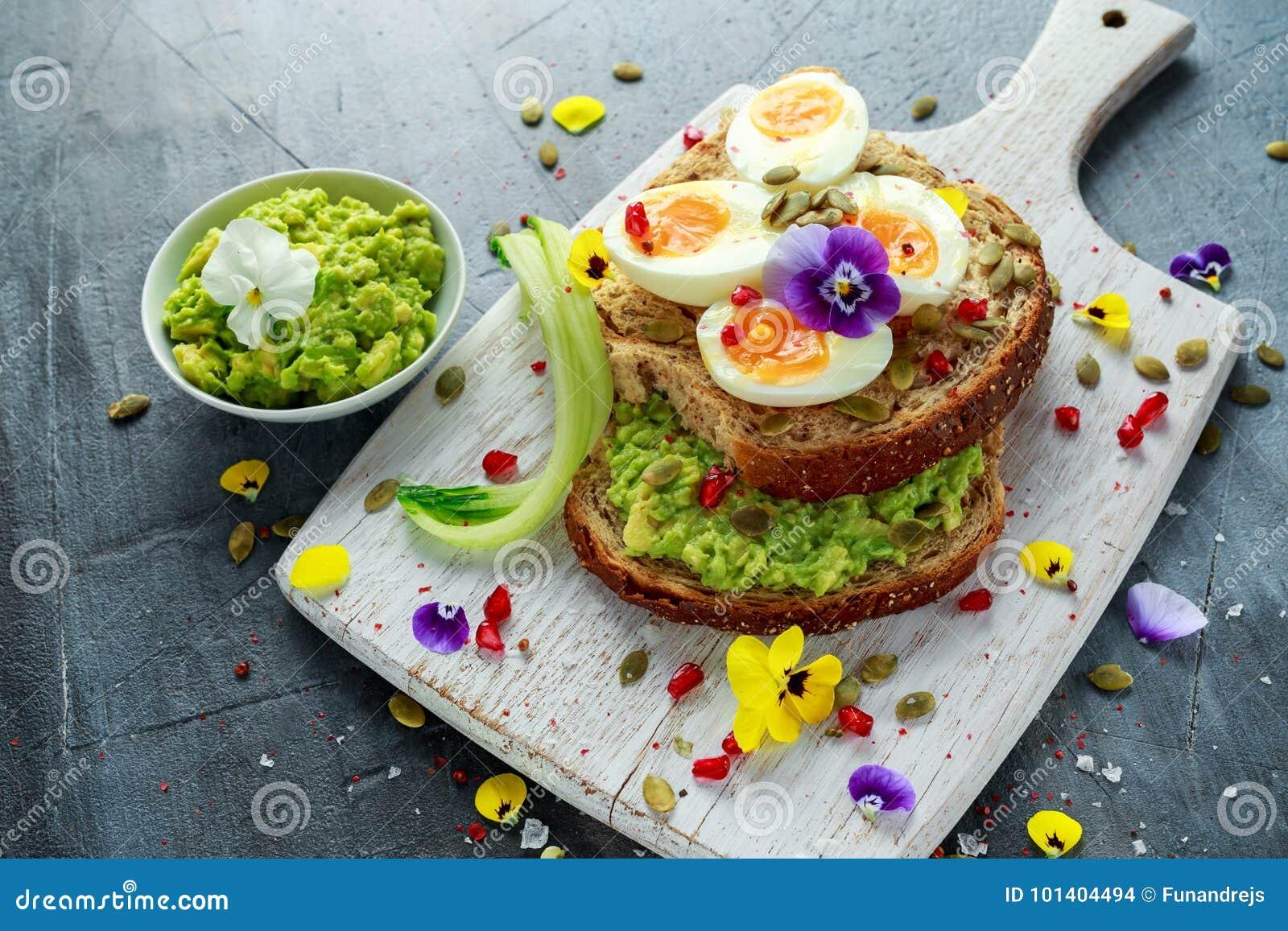 Den smakliga smörgåsen med avokadot kokade ägg, pumpa kärnar ur, och den ätliga altfiolen blommar i ett vitt bräde sund mat