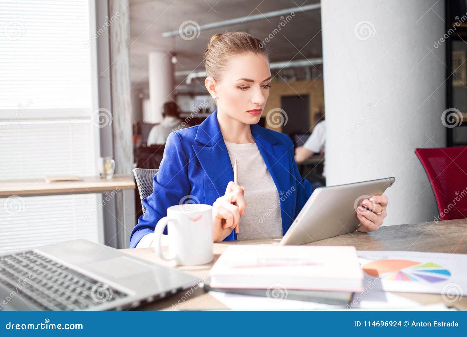 Den smarta och snygga kvinnan sitter på tabellen och ser till minnestavlan Hon studerar Flickan är mycket