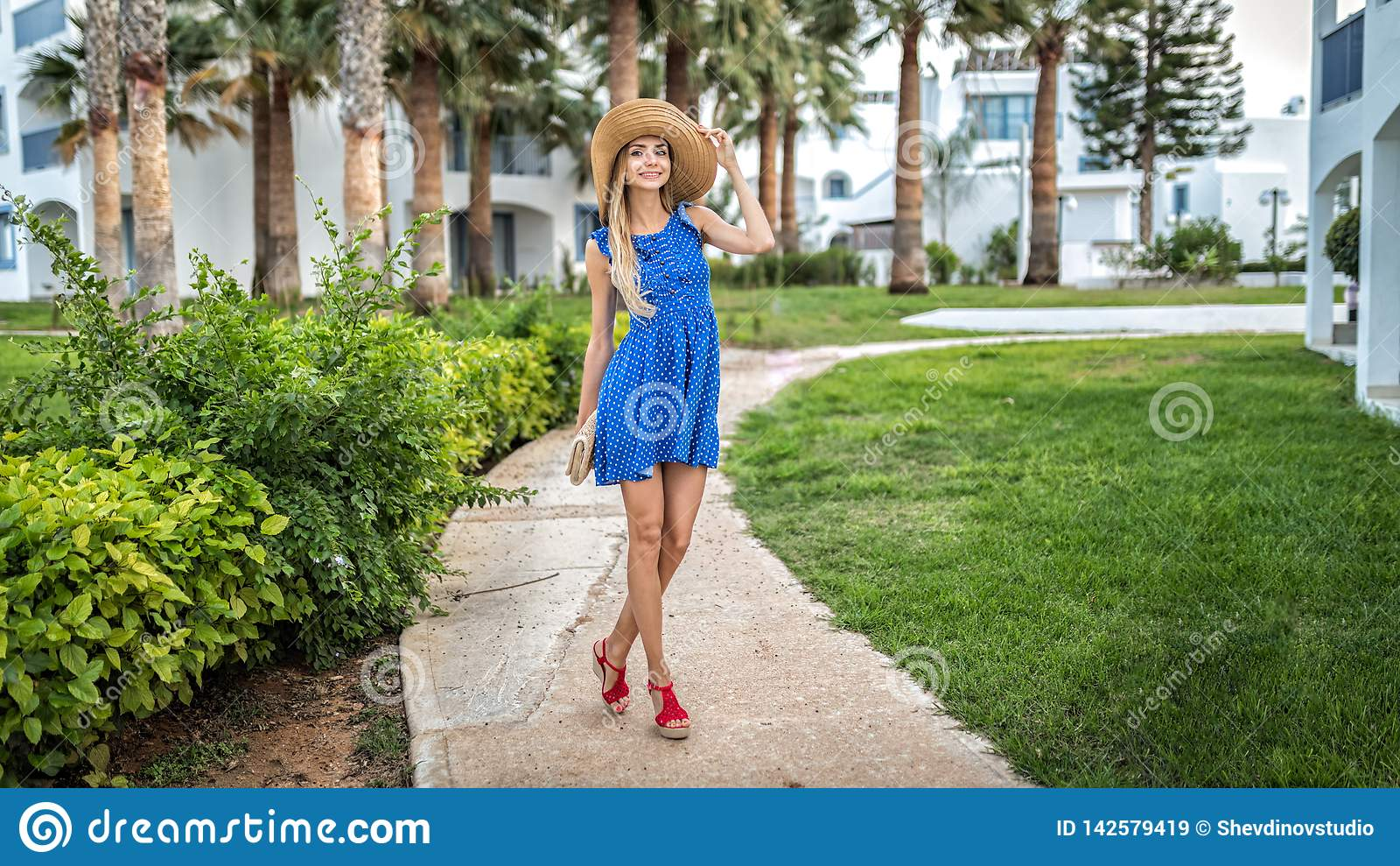 In den Sommerferien steht ein angemessenes behaartes schönes junges nettes Mädchen auf einer Palmengasse an den Feiertagen