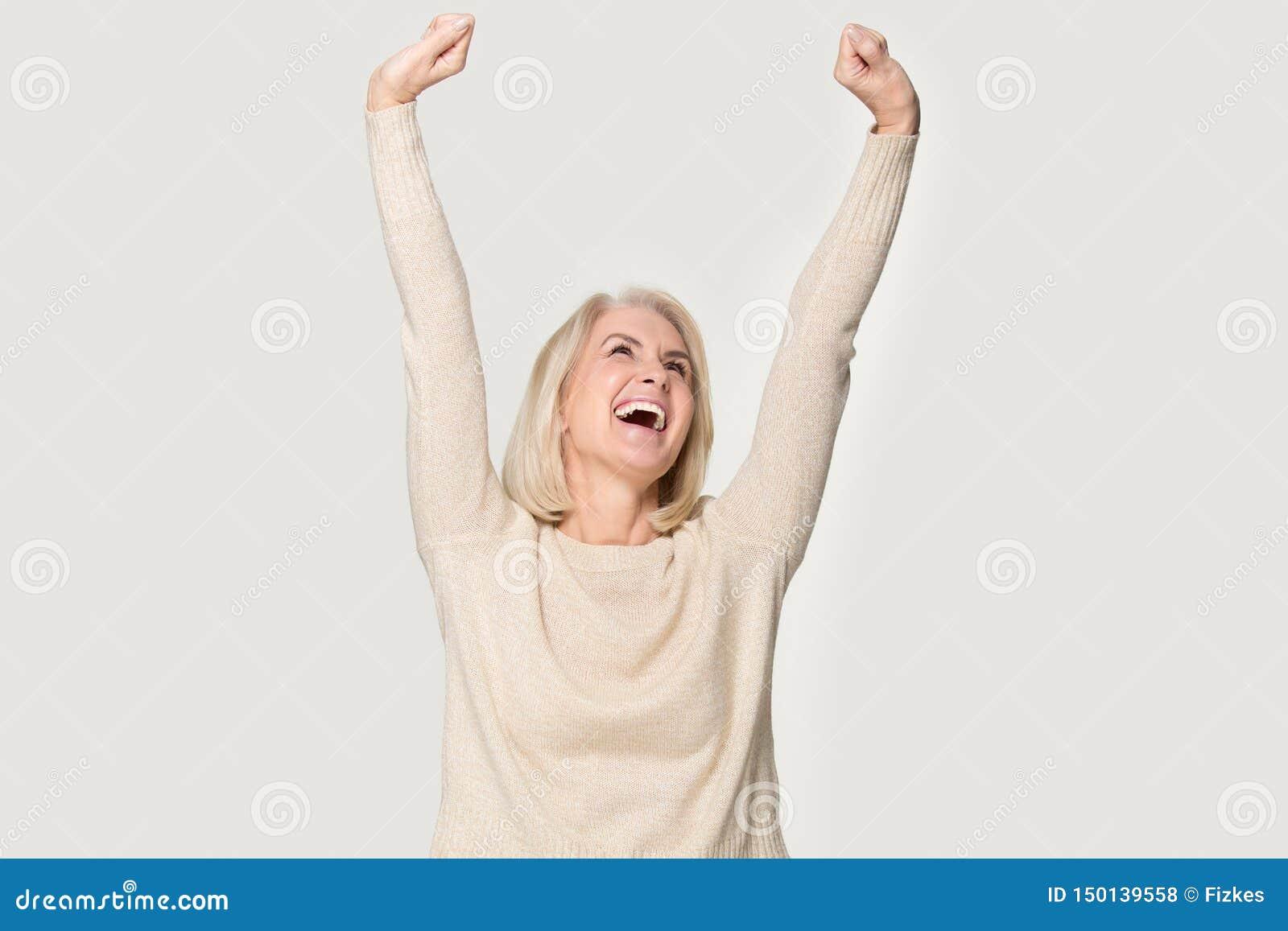 Den spännande höga kvinnan lyftte sträckta händer känner det lyckliga studioskottet