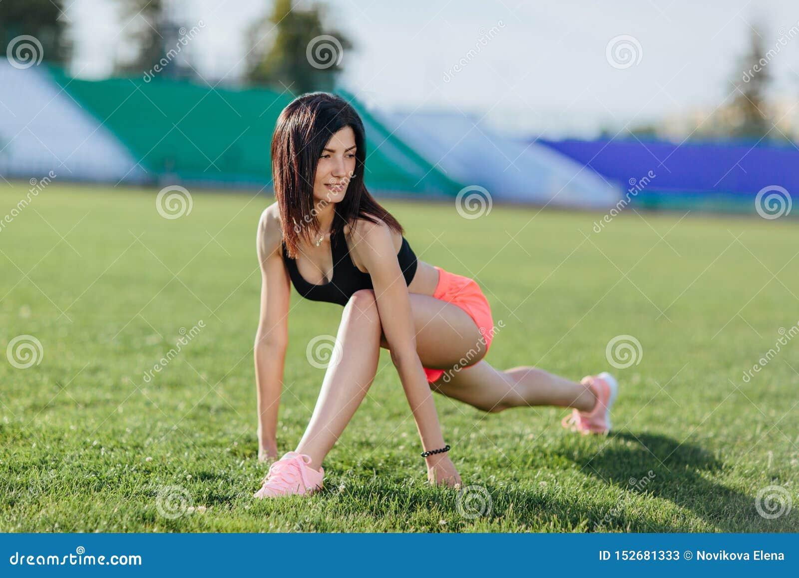 Den sportiga kvinnabrunettlöparen i sportkläder som gör genomkörareperioder på fältet i sportar, passar i sommaren på en varm sol