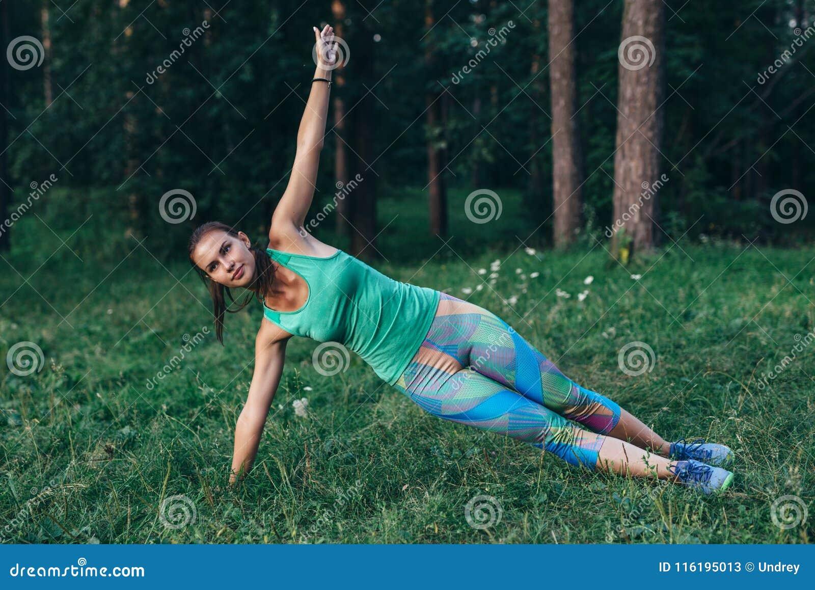 Den sportiga slanka idrottskvinnan som gör sidoplankayoga, poserar anseende på gräs i sommarmorgon