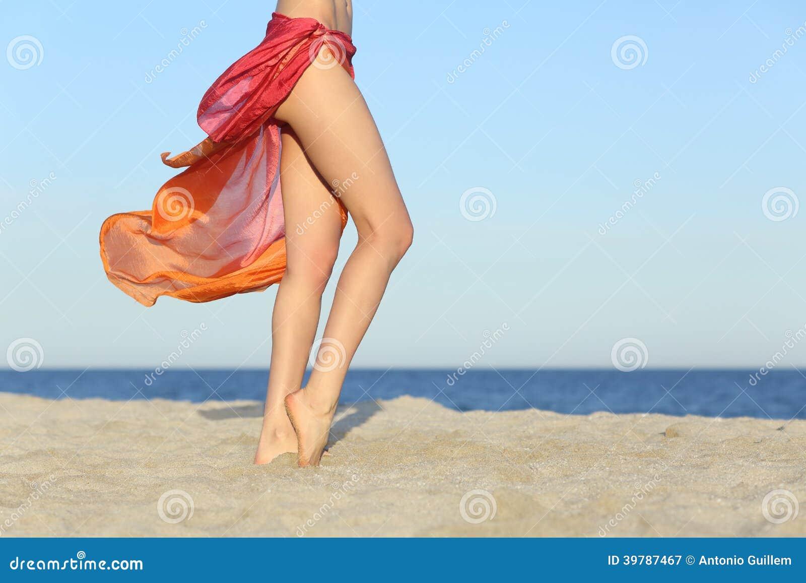 Den stående kvinnan lägger benen på ryggen att posera på stranden som bär en pareo