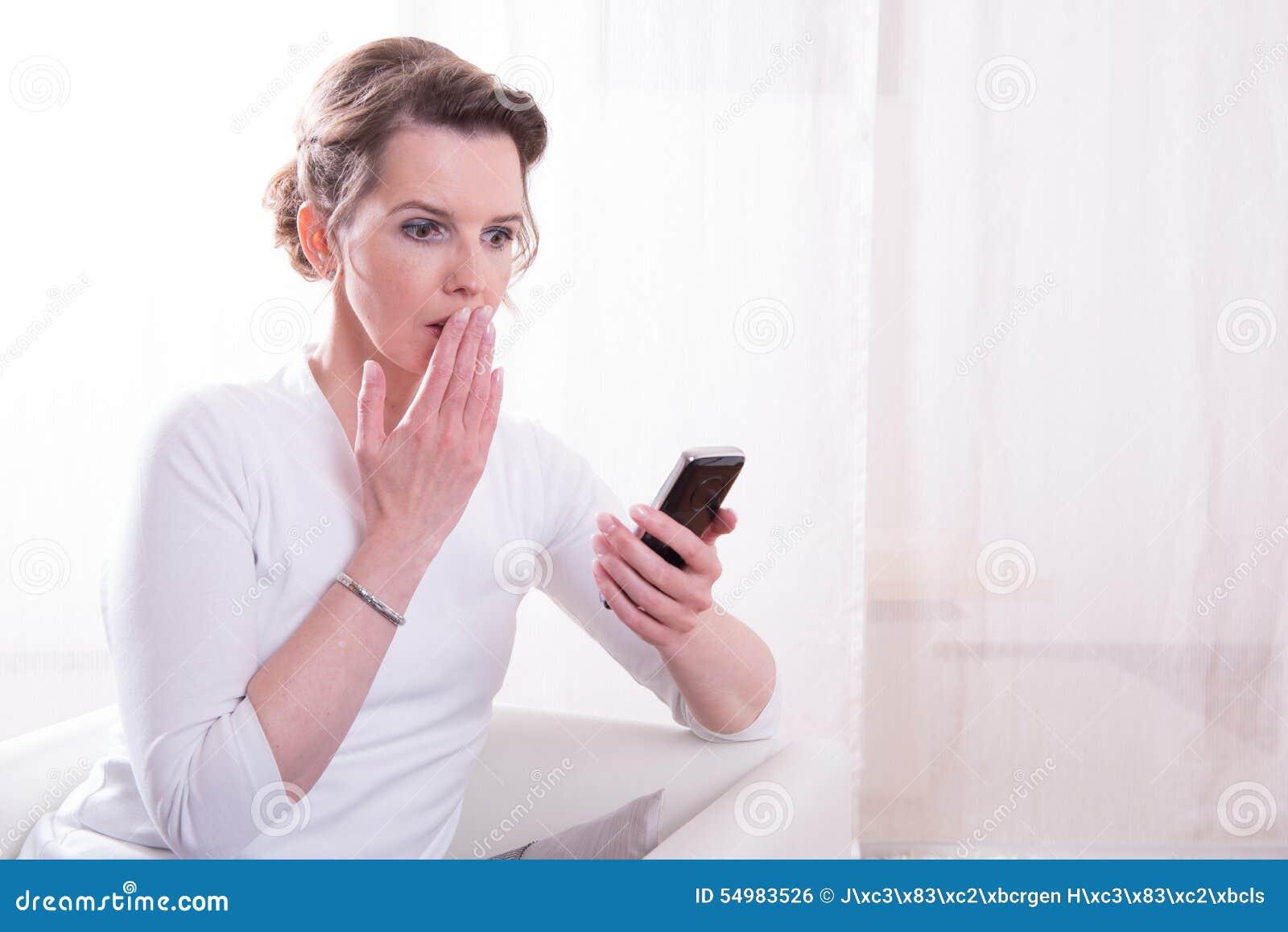 Den starka kvinnan frightendeds av meddelandet på smartphonen