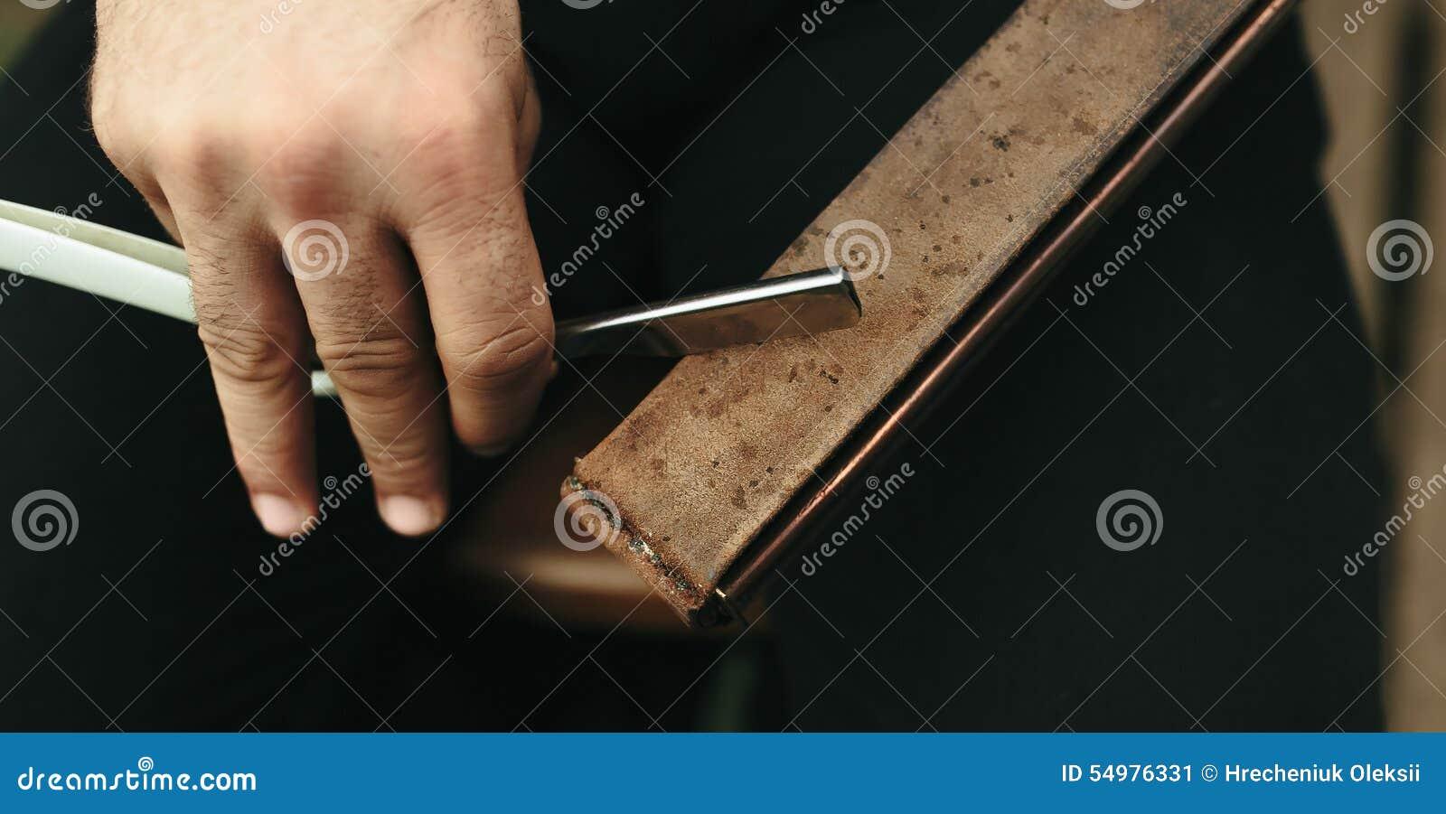 Den starka mannen vässar den gamla rakkniven