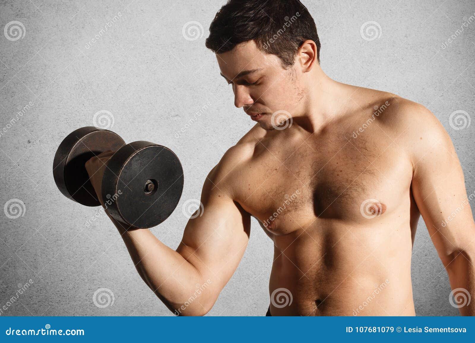 Den starka muskulösa kroppsbyggaren gör bicepsövningar med hantlar i händer som är involverade i den sunda aktiva livsstilen som
