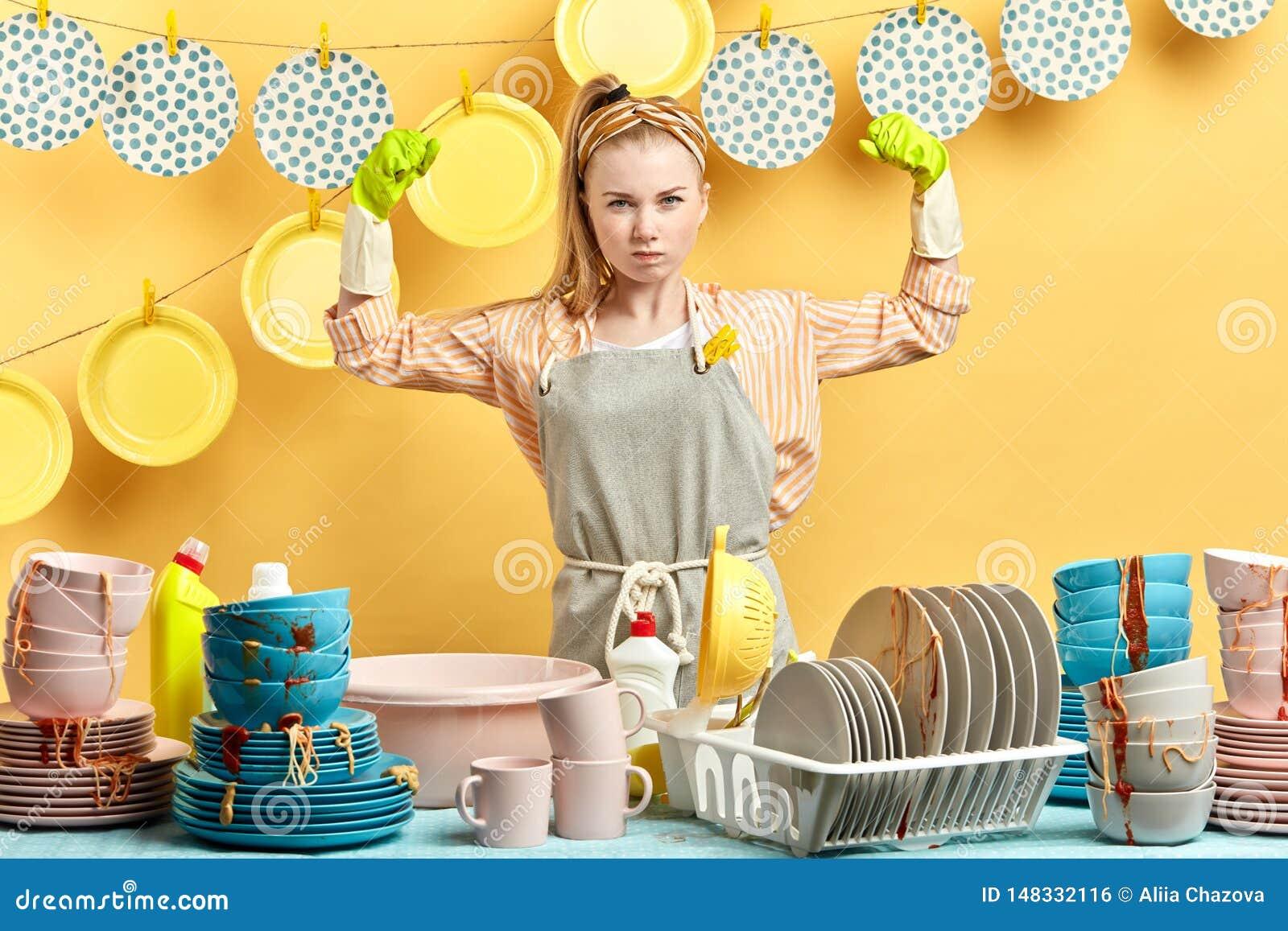 Den starka rynka pannan kvinnan med lyftta armar är klar att tvätta disken efter parti