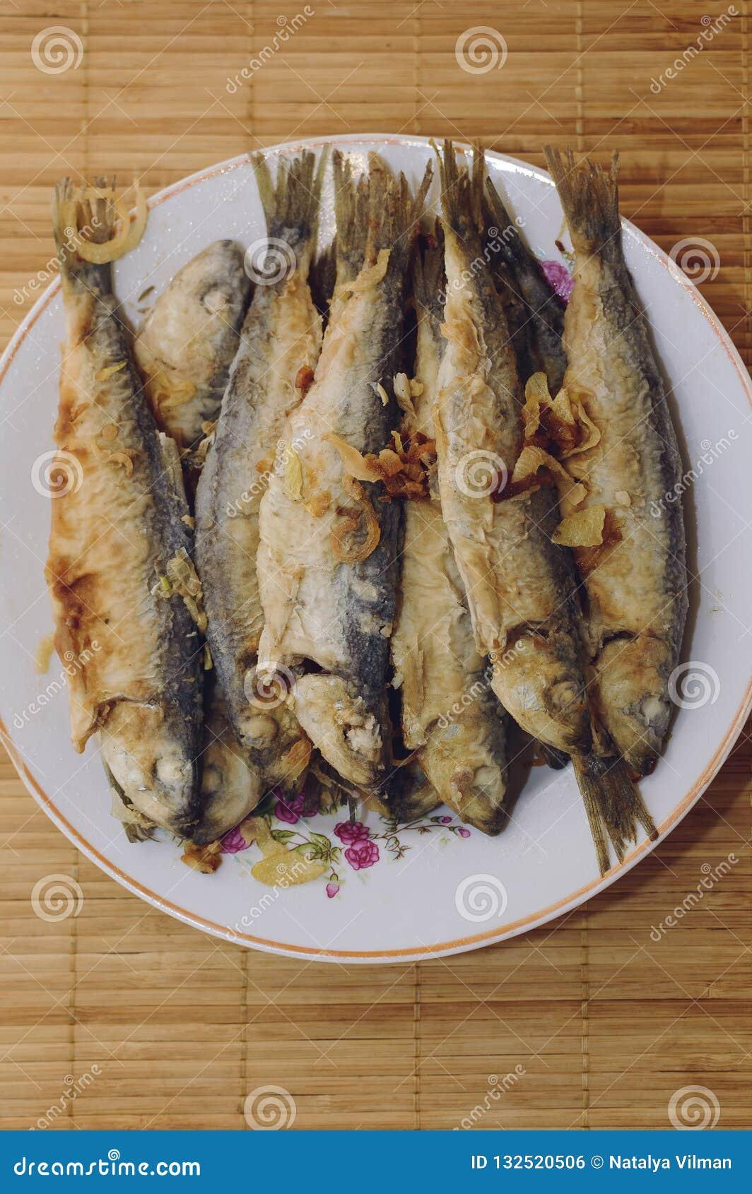 Den stekte fiskströmmingen ligger på en platta på en bambuservett