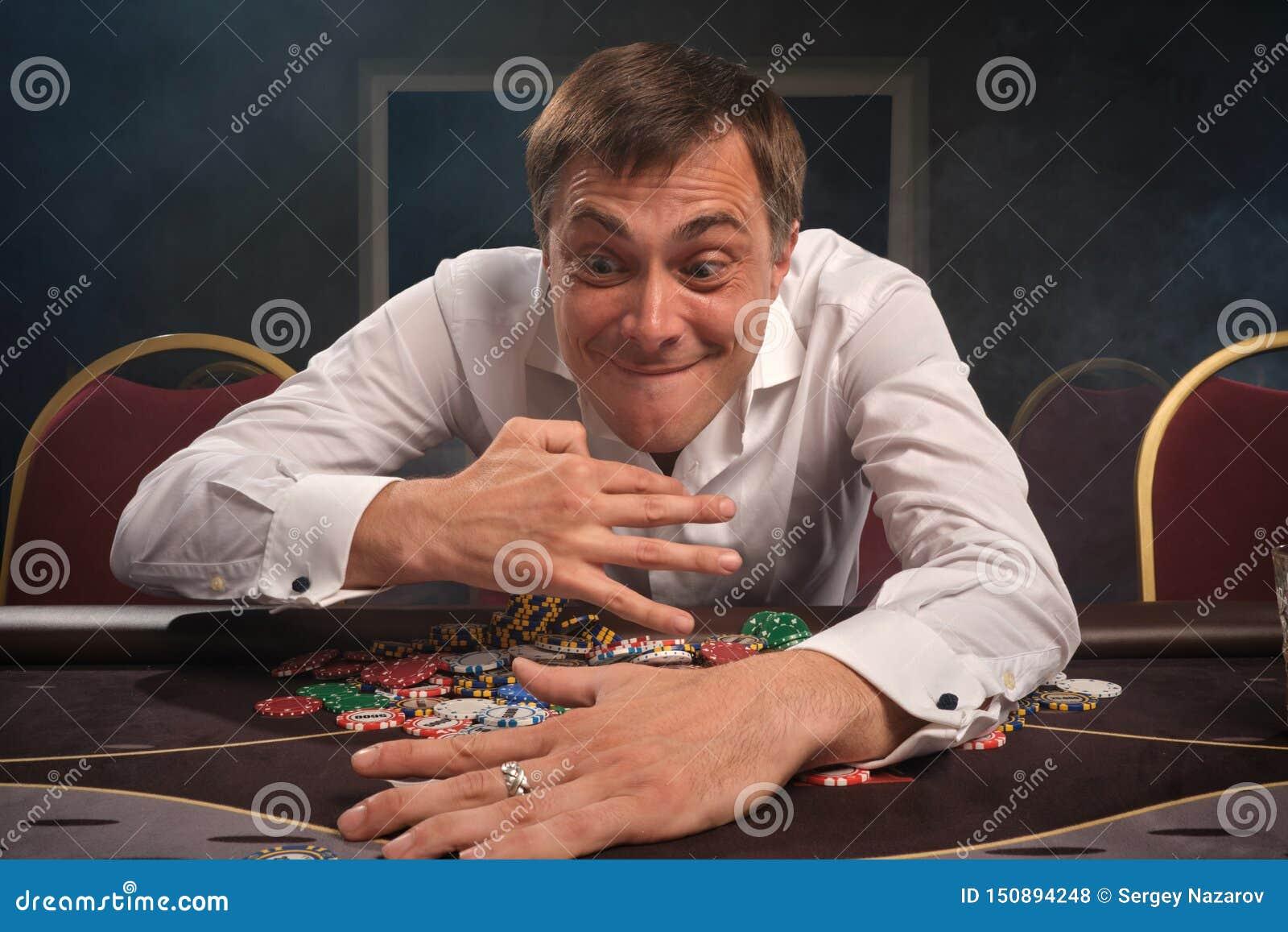 Den stiliga emotionella mannen spelar poker som sitter på tabellen i kasino
