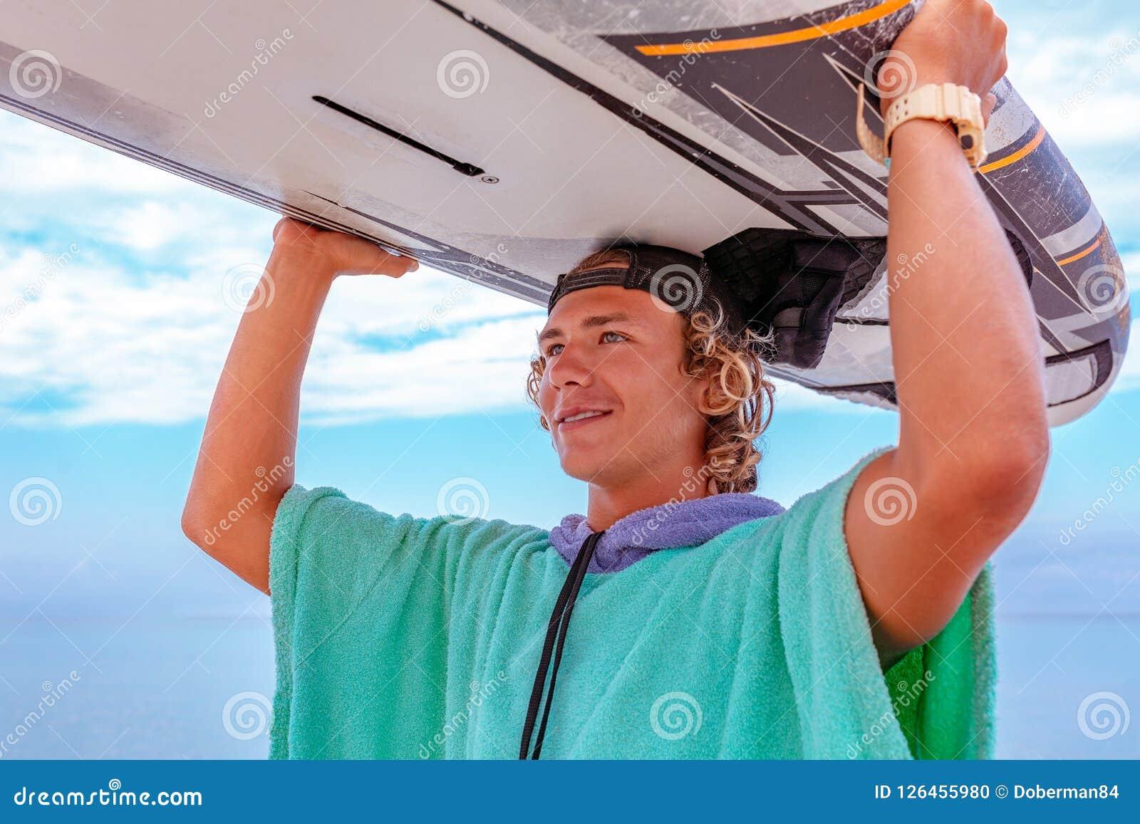 Den stiliga mannen går med vitmellanrumssurfingbrädan väntar på vågen att surfa fläcken på havshavkusten Begrepp av sporten