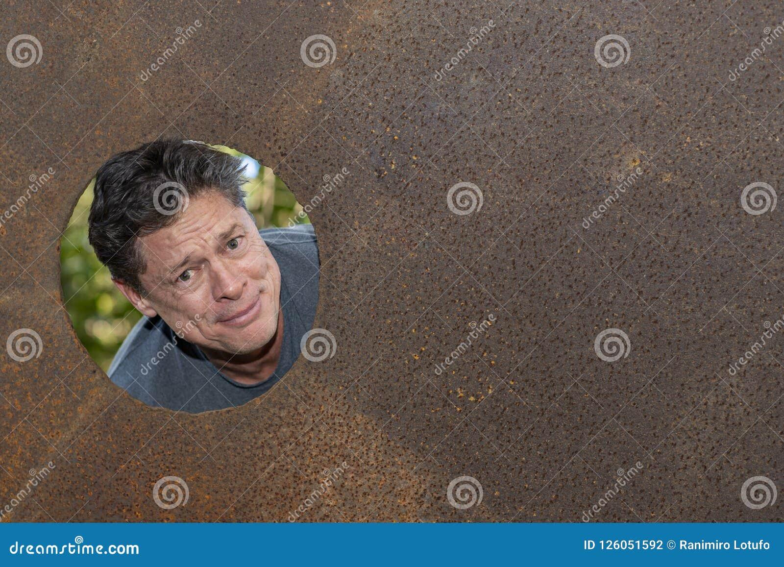 Den stiliga mogna mannen i järnplattahålet som bort ser, grinar, lyckligt, nöjt