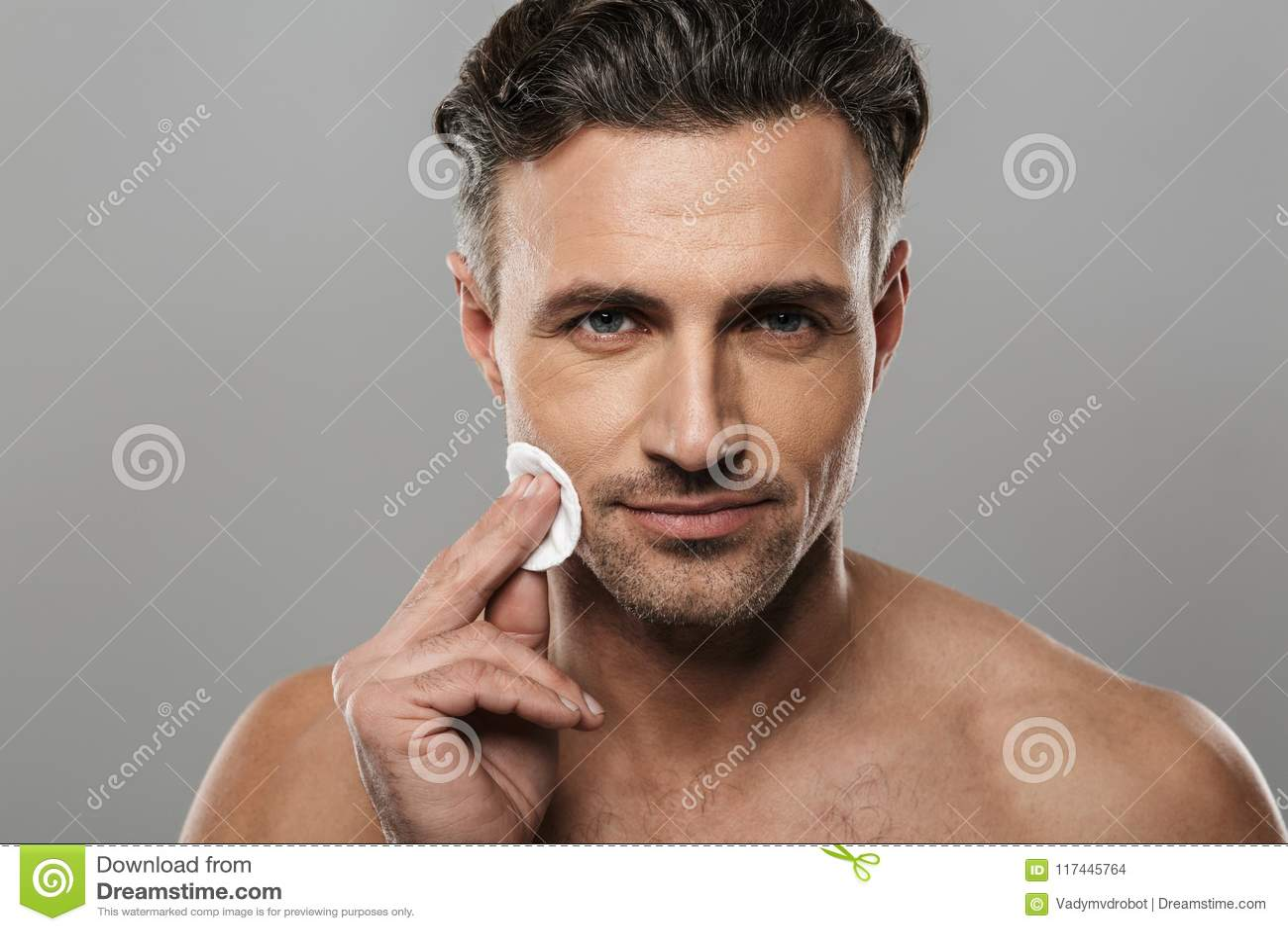 Den stiliga mogna mannen tar omsorg av hans hud
