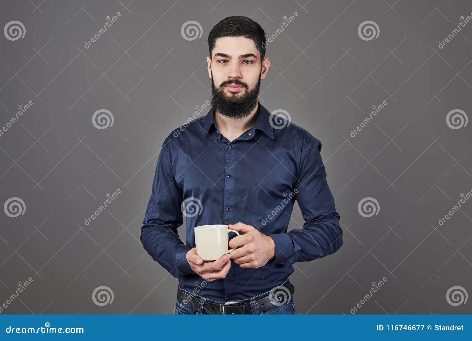 Den stiliga skäggiga mannen med det stilfulla hårskägget och mustaschen på allvarlig framsida i hållande vit kopp för skjorta ell
