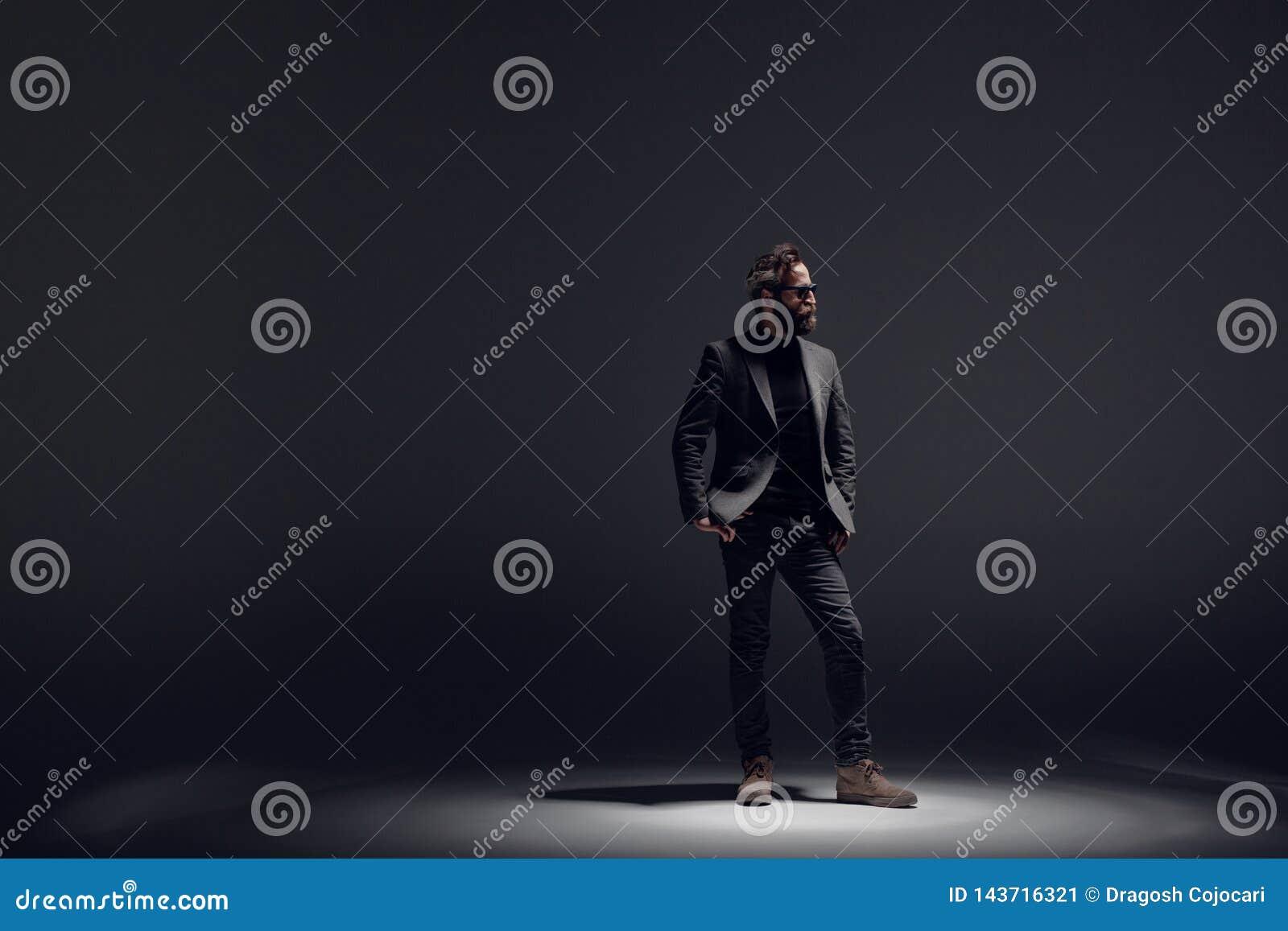Den stiliga skäggiga mannen som bär i svart dräkt, poserar i profil i studio, på en mörk lighttbakgrund