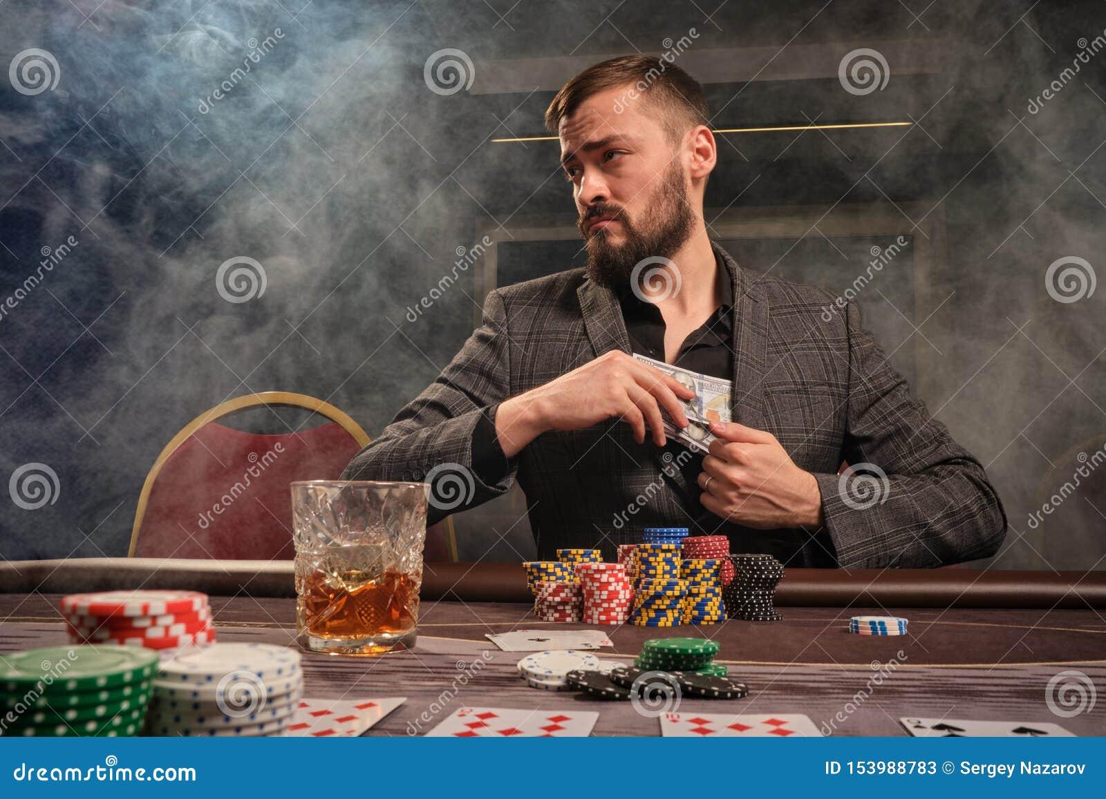 Den stiliga skäggiga mannen spelar poker som sitter på tabellen i kasino