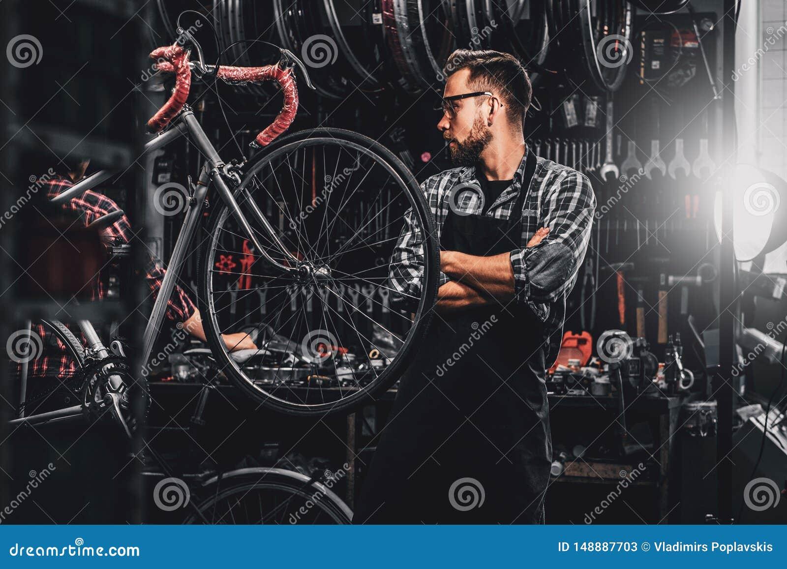 Den stiliga sk?ggiga mannen i exponeringsglas st?r n?ra den fasta cykeln p? hans eget seminarium