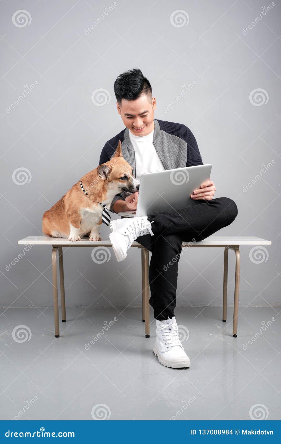 Den stiliga unga affärsmannen använder bärbara datorn, medan sitta med hans hund på stol