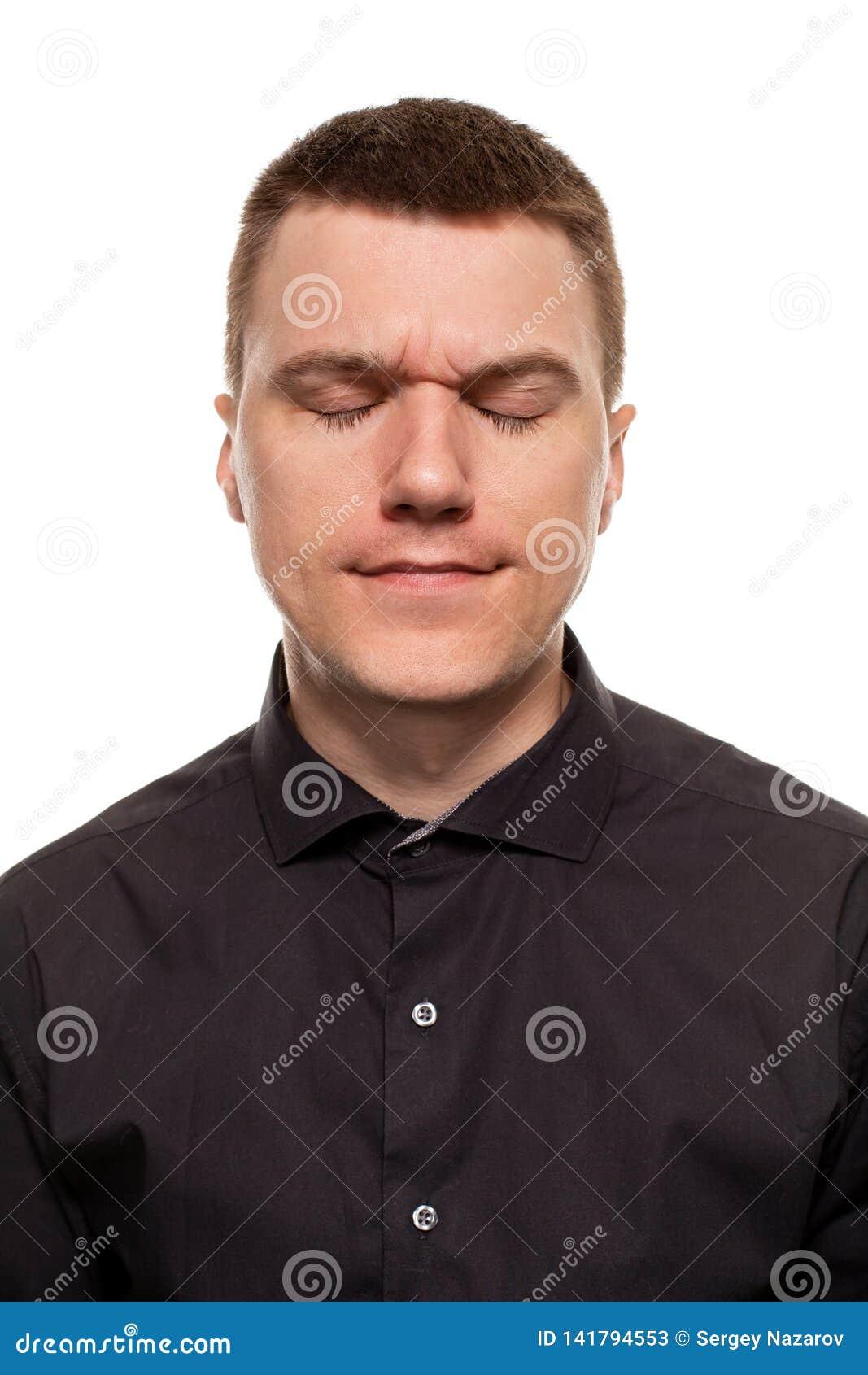 Den stiliga unga mannen i en svart skjorta gör framsidor, medan stå isolerad på en vit bakgrund