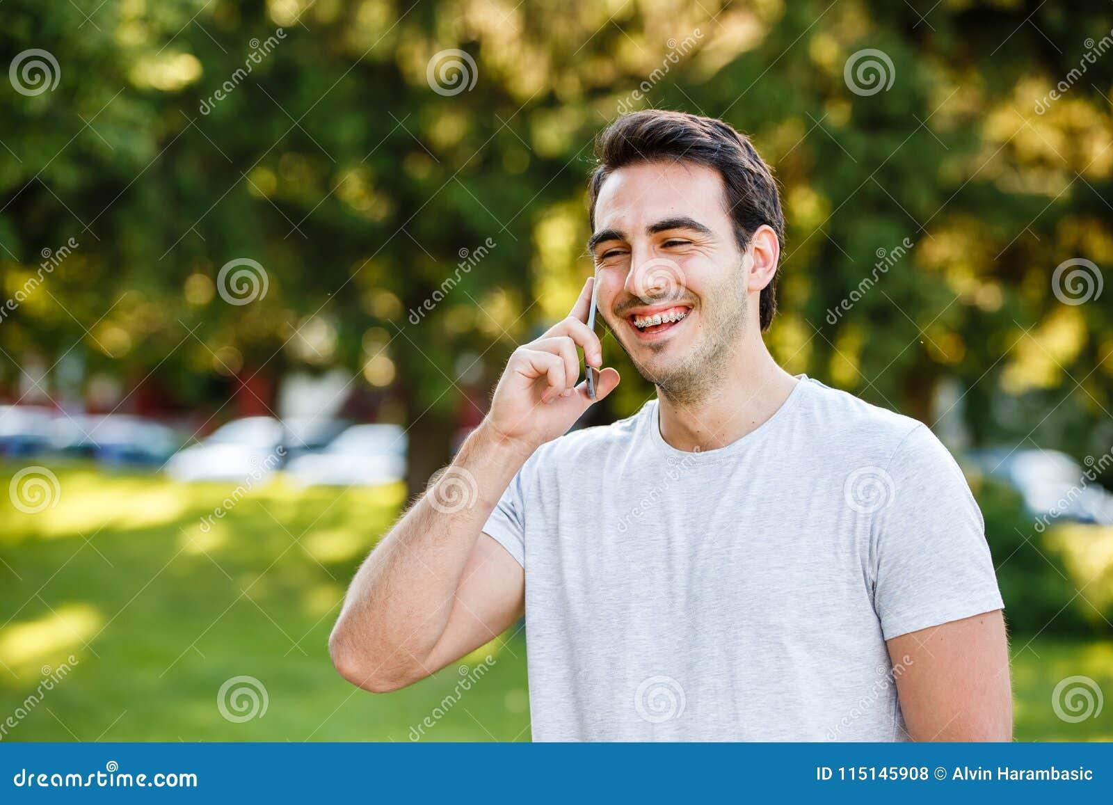Den stiliga unga mannen parkerar in talkig på hans telefon