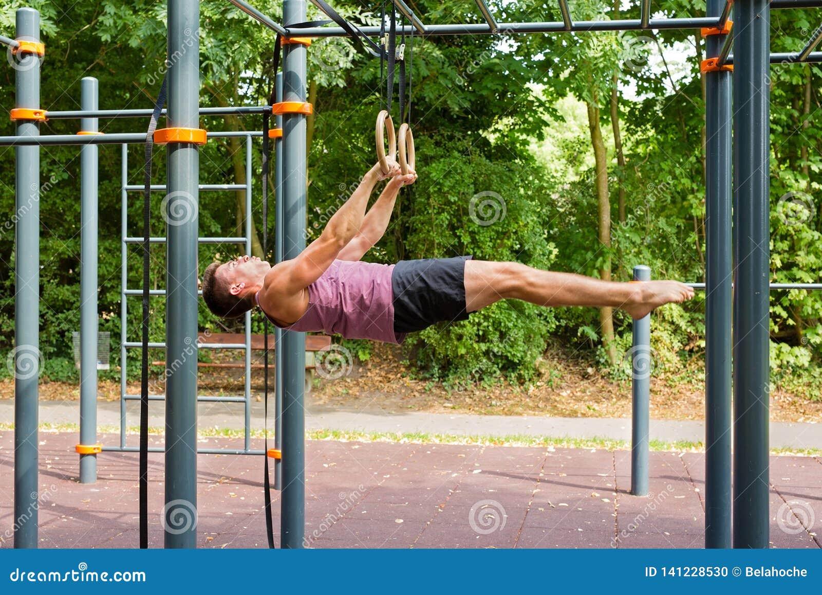 Den stiliga unga mannen som gör gymnastik, ringer genomkörare: