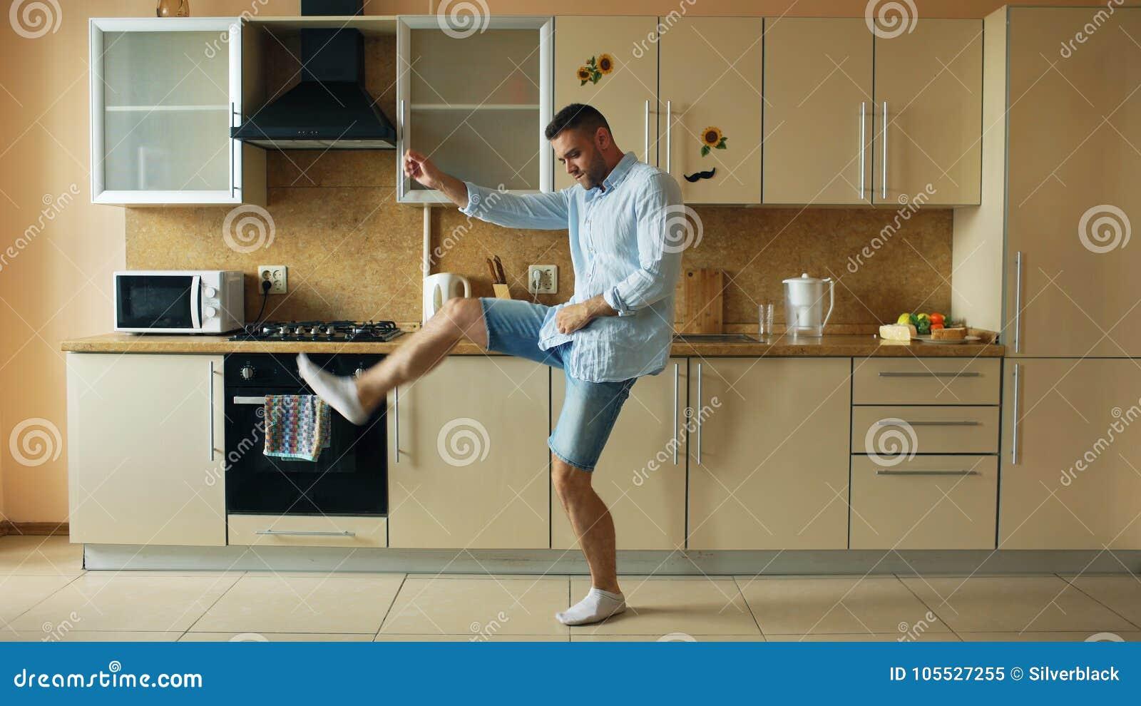 Den stiliga unga roliga mandansen i kök hemma i morgonen och har gyckel på ferier