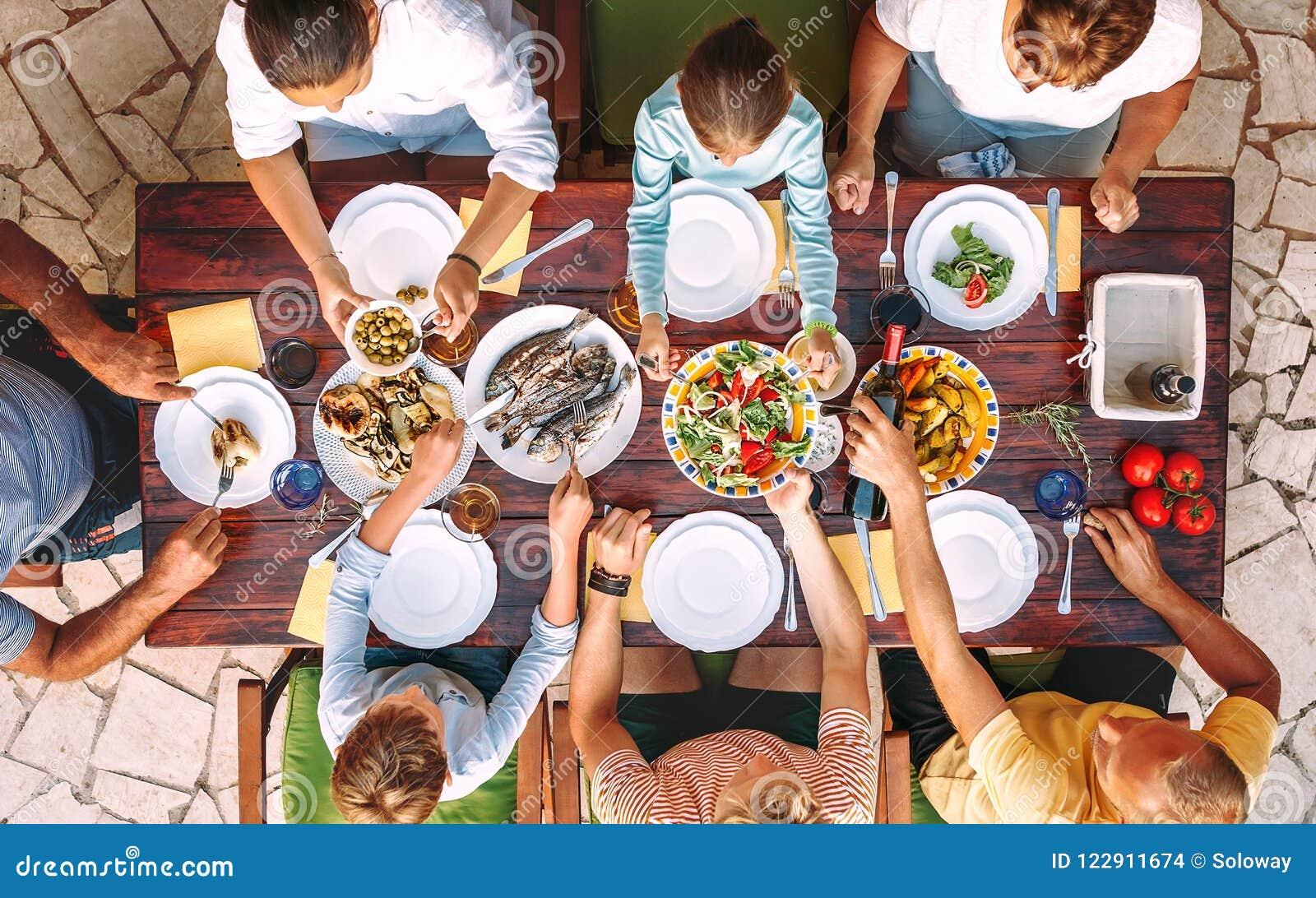 Den stora familjen har en matställe med nytt lagat mat mål på öppen trädgård t