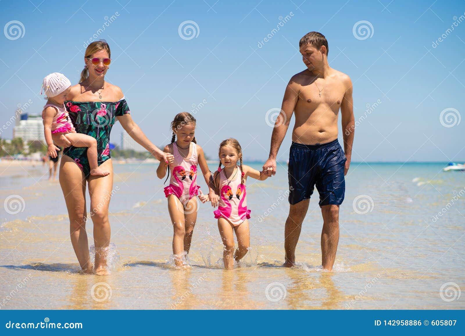 Den stora lyckliga familjen har gyckel på stranden begrepp av en stor familj på havet Stranden danar