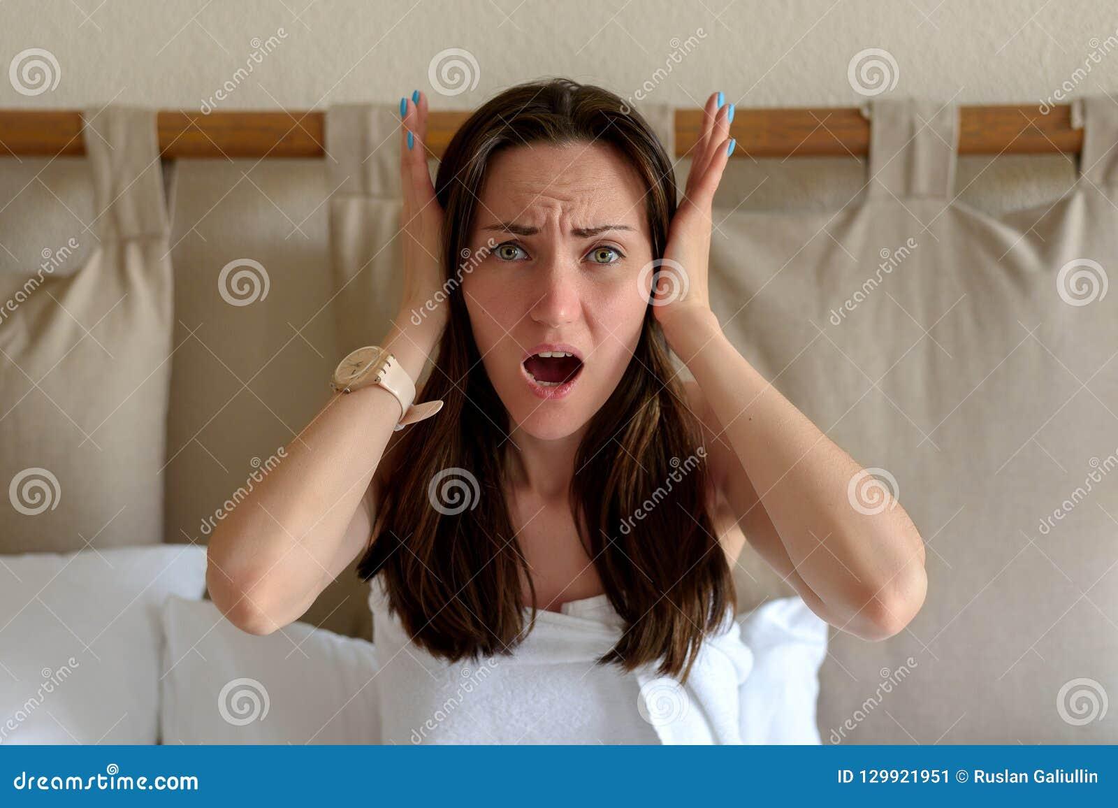 Den stora ståenden av en kvinna som rymmer hennes huvud med hennes händer, begreppet av huvudvärken, migrän, bullriga grannar, ru