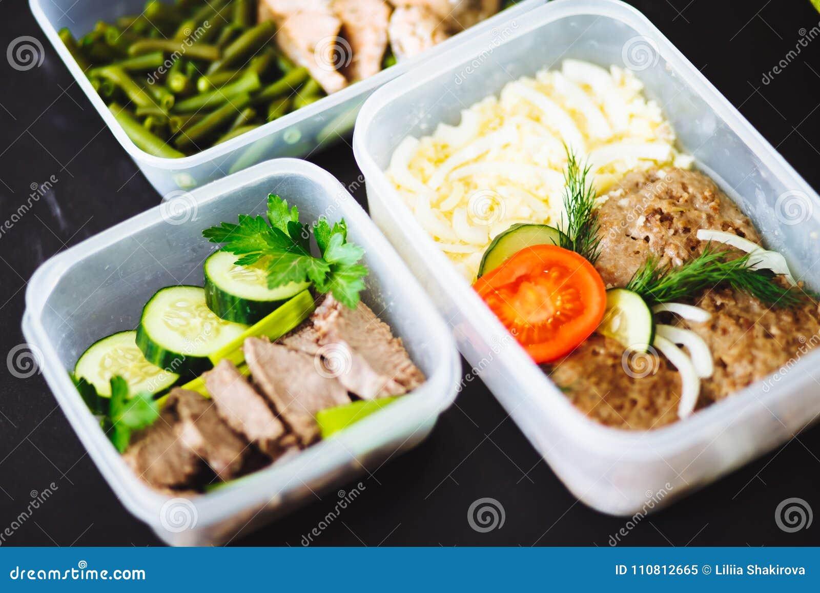 Den sunda maten i behållarna på svart bakgrund: mellanmål matställe, lunch Den bakade fisken, bönor, nötköttkotletter, mosade pot