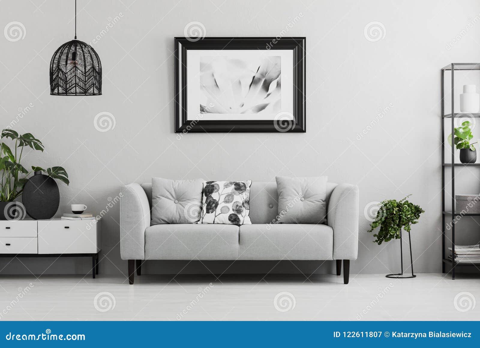 Den svarta industriella bokhyllan och en växt står bredvid en stoppad soffa i en grå vardagsruminre med stället för en kaffeflik
