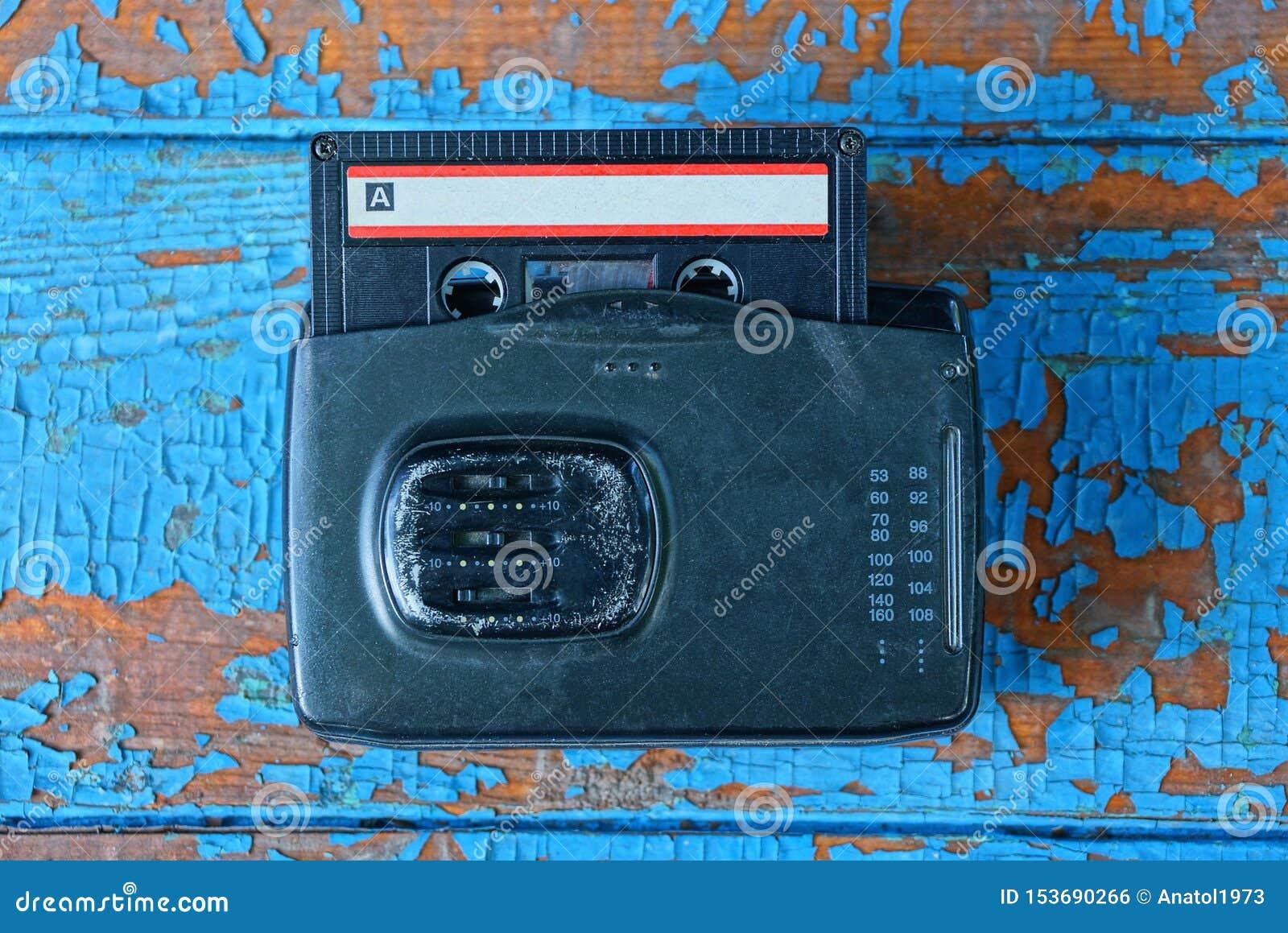 Den svarta ljudsignal spelaren med en kassett ligger på en sliten blå tabell