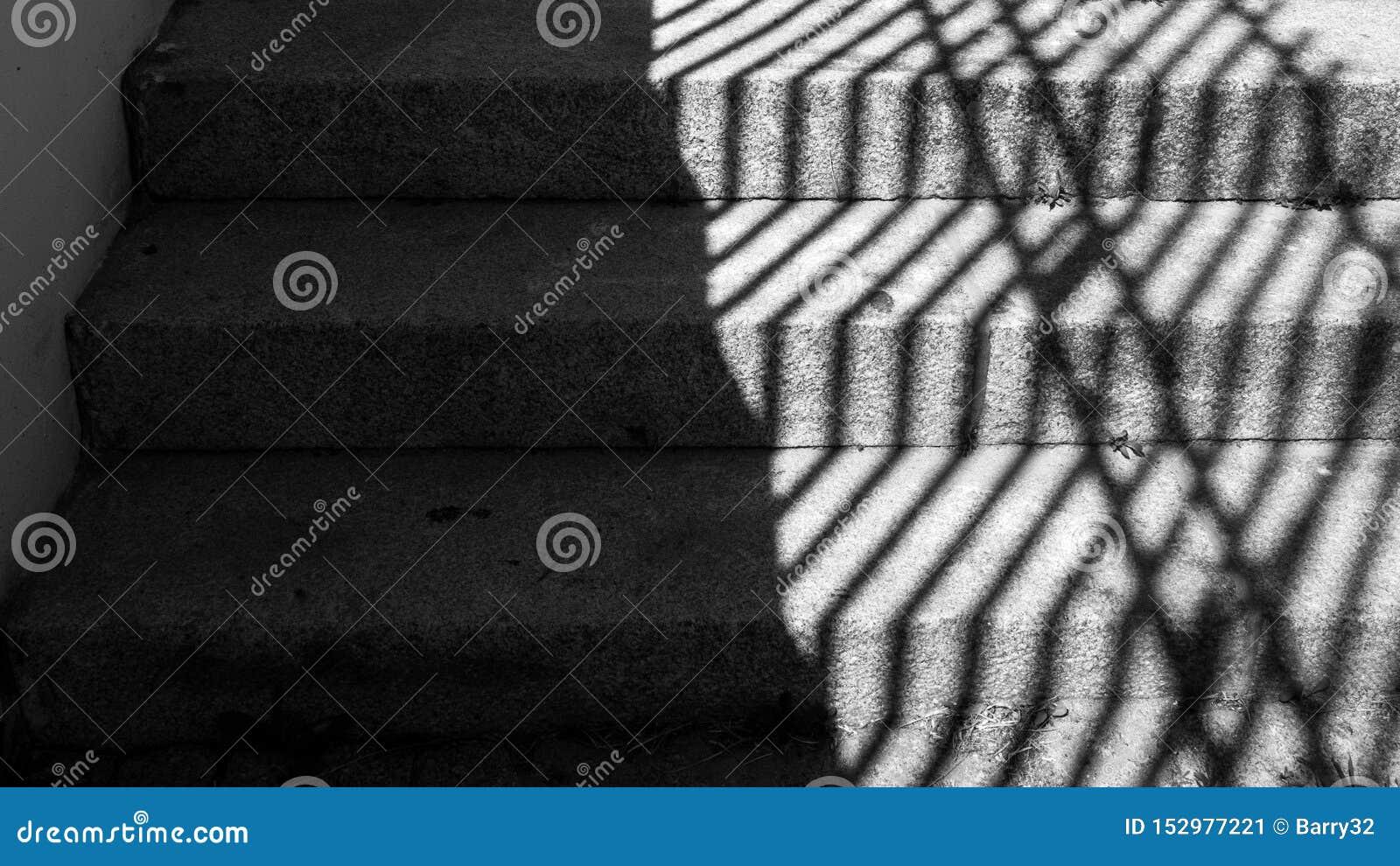 Den svartvita bilden av gammalt stenar moment med hårda skuggor