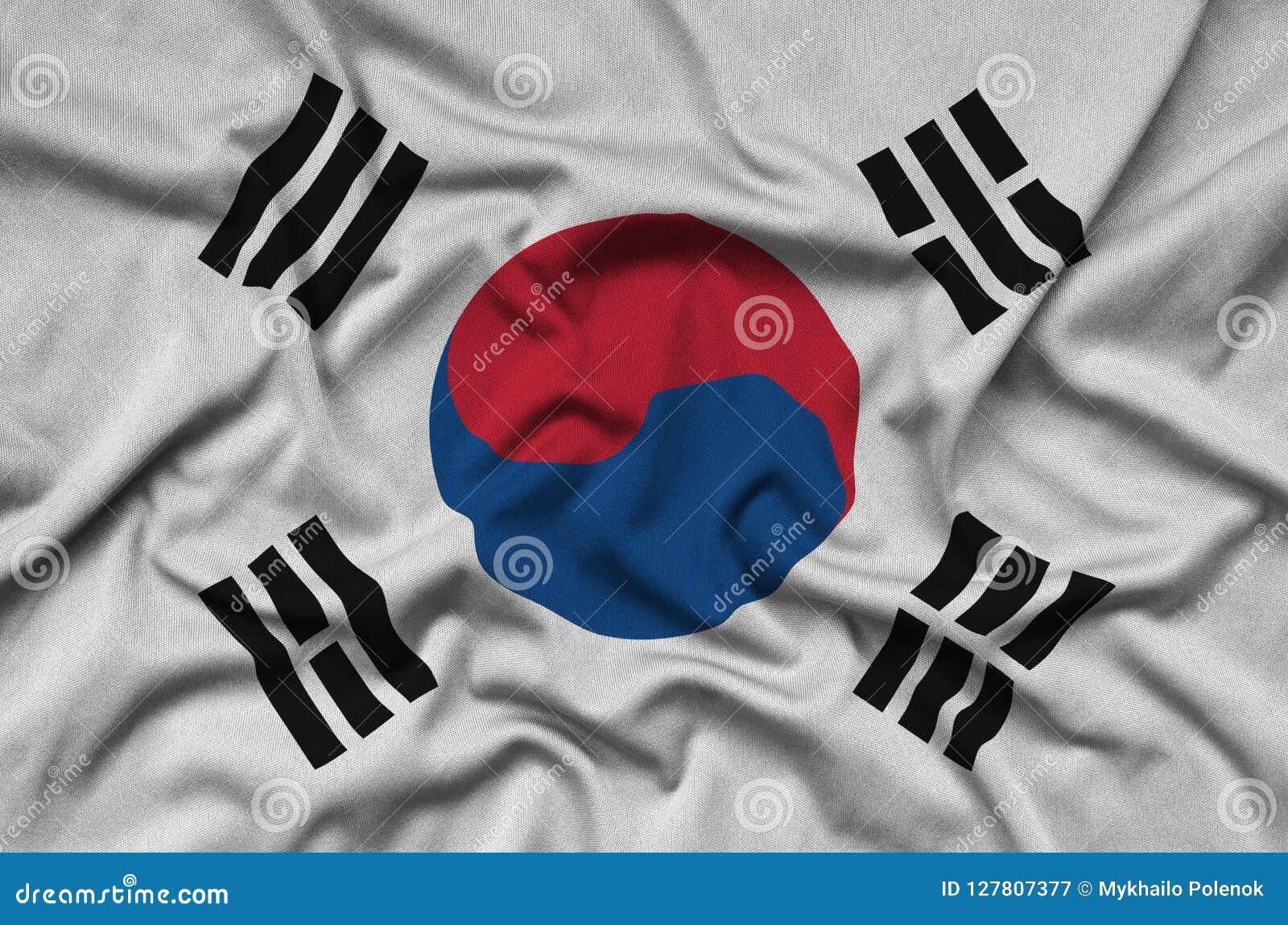 Den Sydkorea flaggan visas på ett sporttorkduketyg med många veck Baner för sportlag