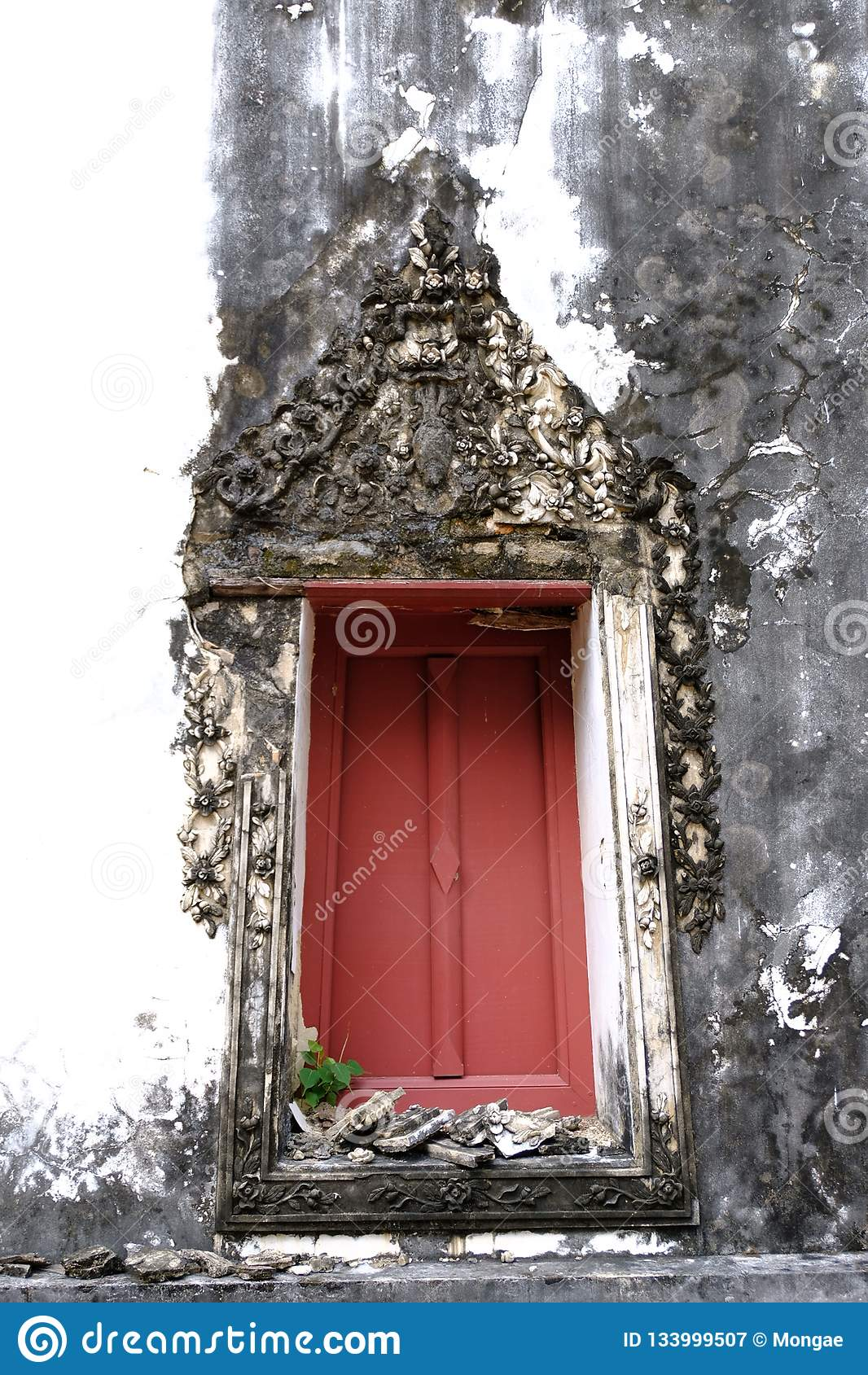 Den thailändska konststuckaturen av den forntida fönsterramen med rött trä med den blom- vinrankamodellen för stuckatur