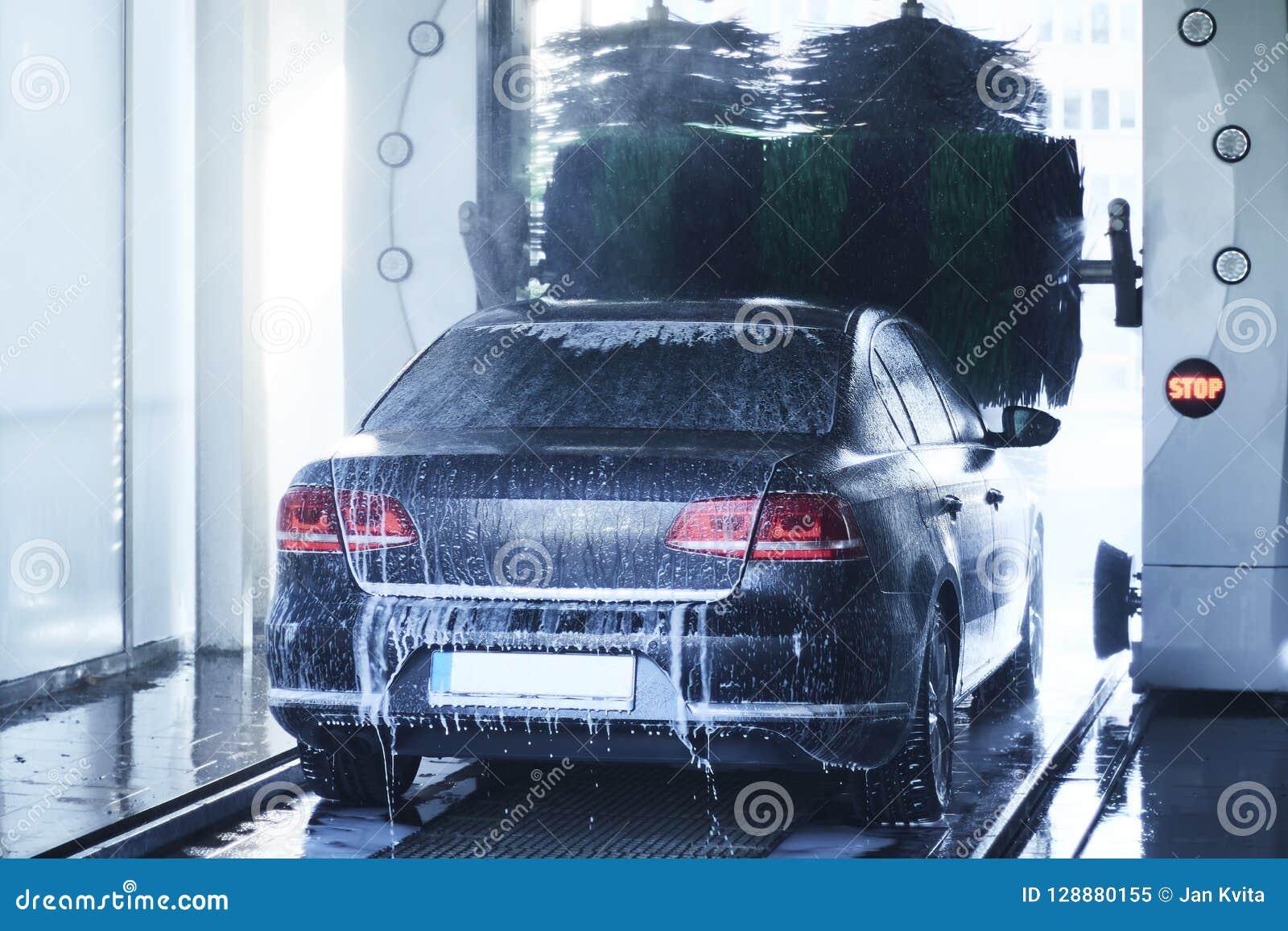 Den tillbaka sikten av en carwash som gör ren en bil med att rotera, borstar