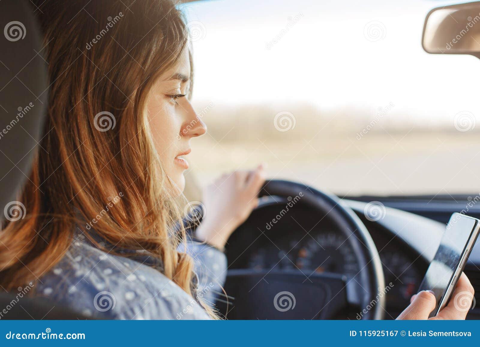 Den tillbaka sikten av den koncentrerade kvinnliga chauffören sitter i bil, rymmer den moderna mobiltelefonen, skriver meddelande