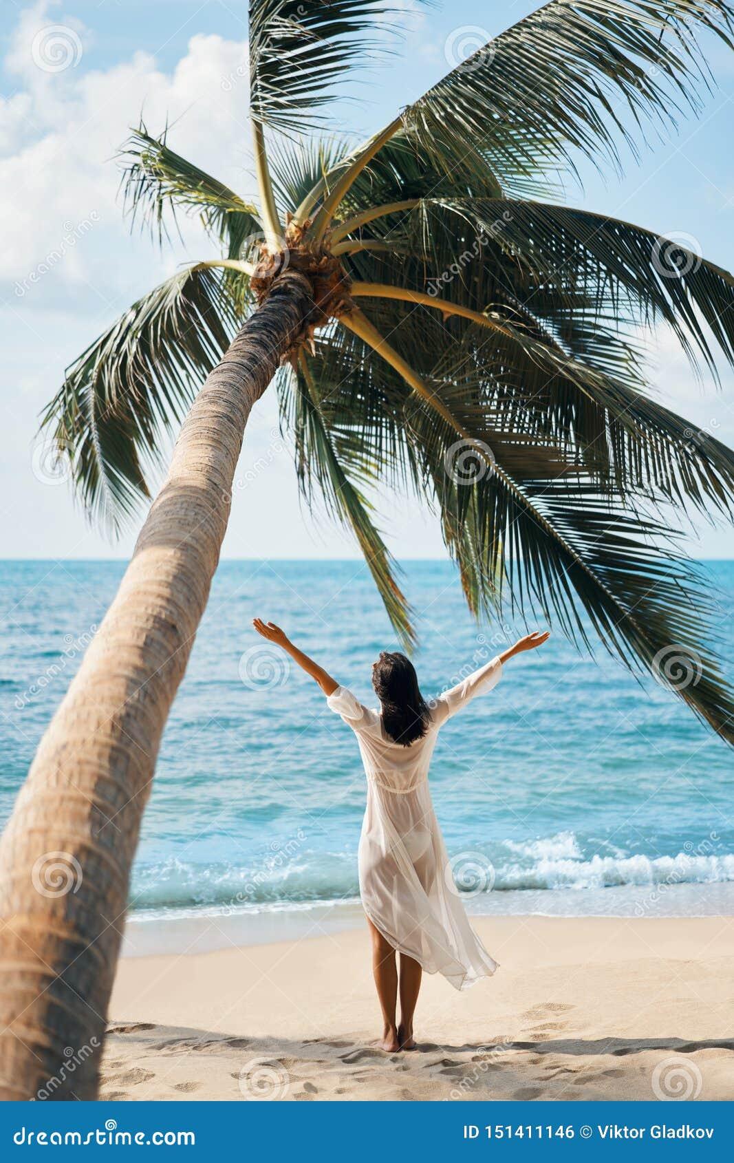 Den tillbaka sikten av den lyckliga unga kvinnan tycker om hennes tropiska strandsemesteranseende under palmträdet