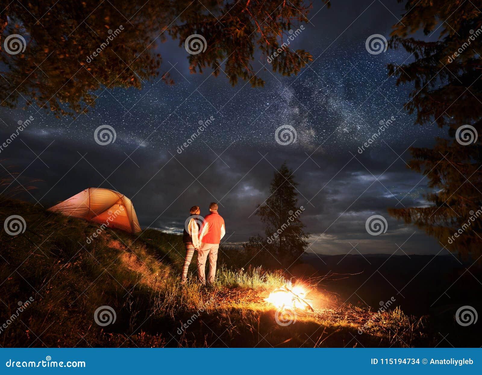 Den tillbaka sikten av vänner rymmer på till händer som tycker om natthimlen med ljusa stjärnor