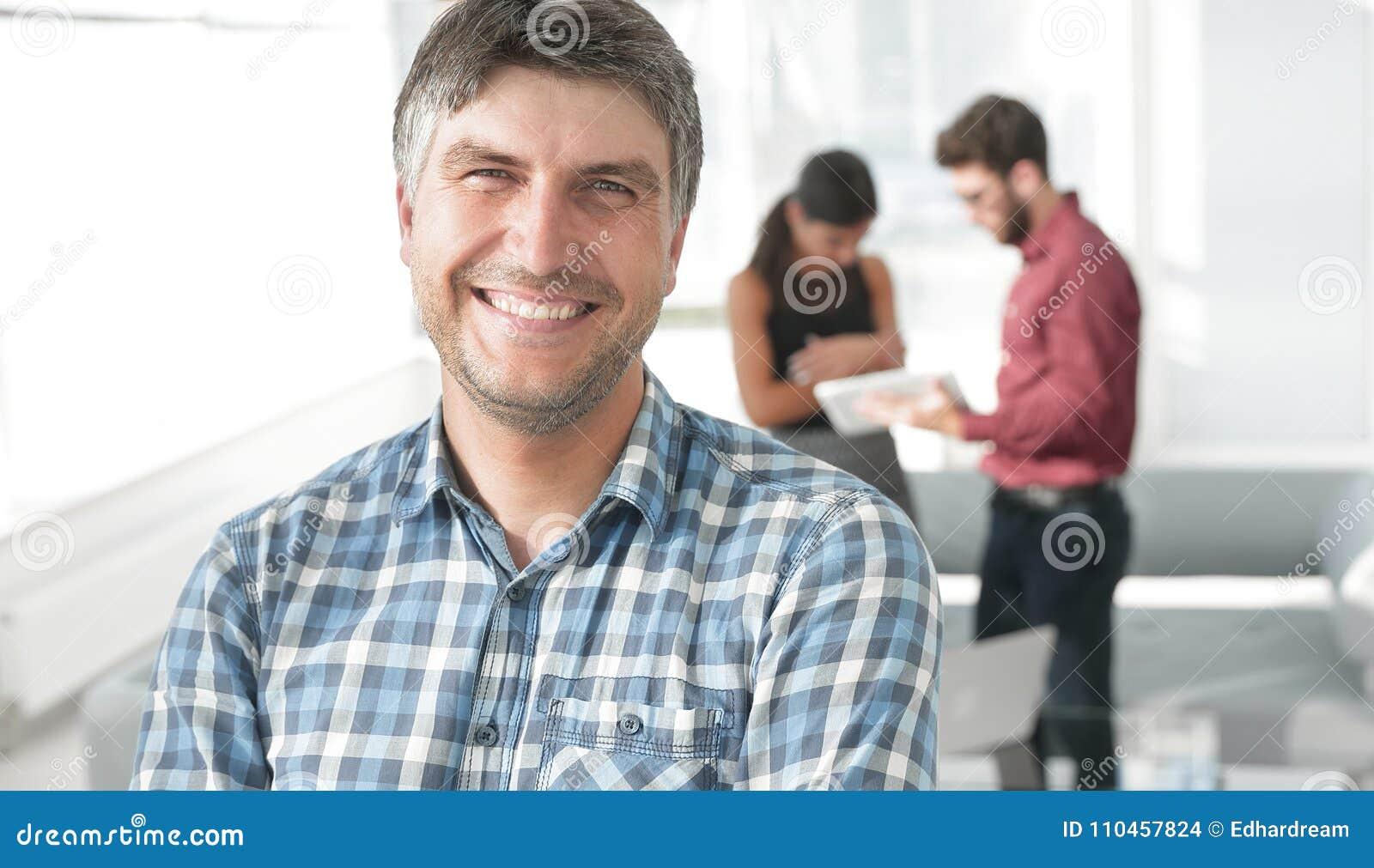 Den tillfälliga affärsmannen med armar korsade anseende i kontoret