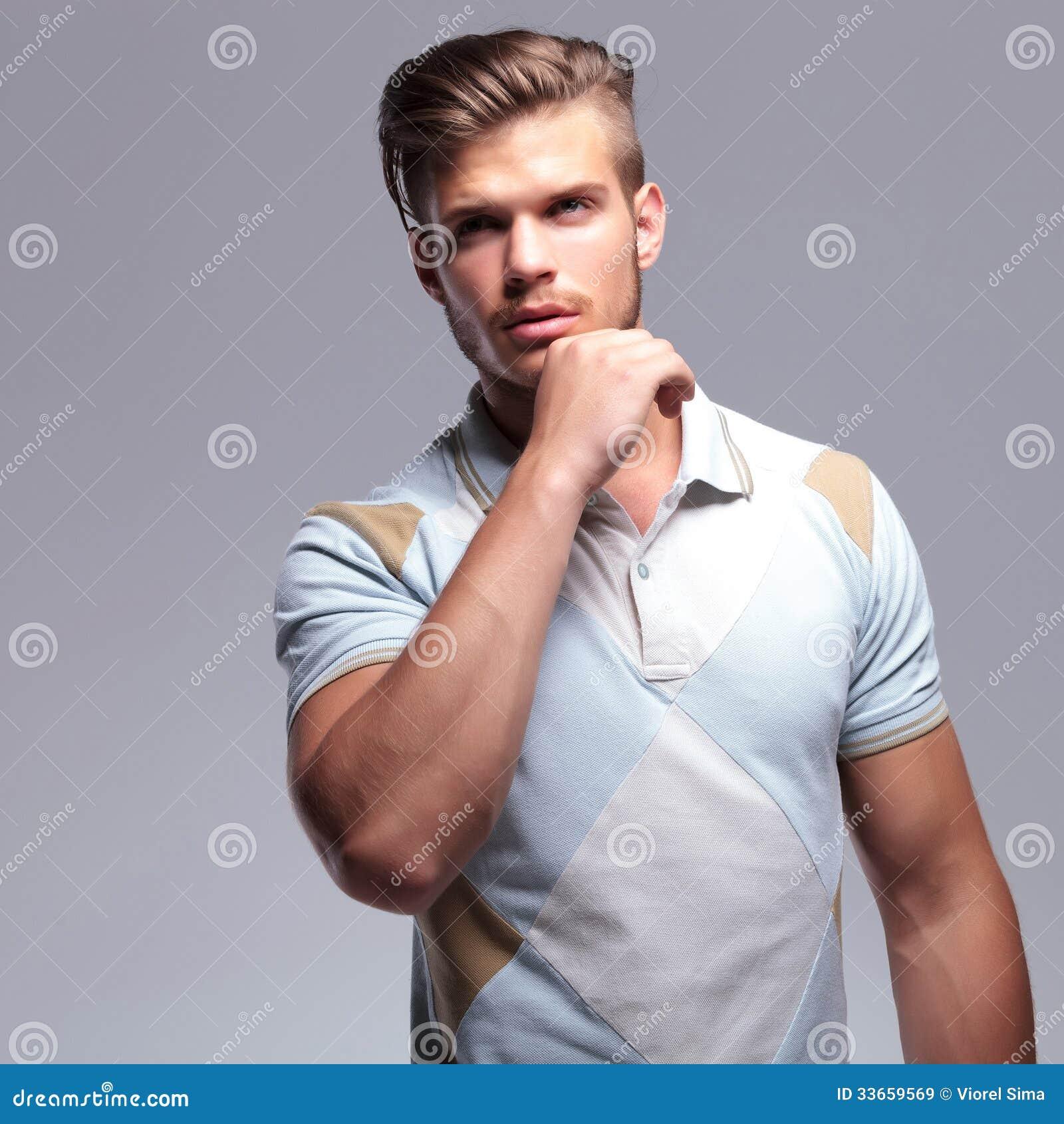 Den tillfälliga mannen med handen på hakan ser bort