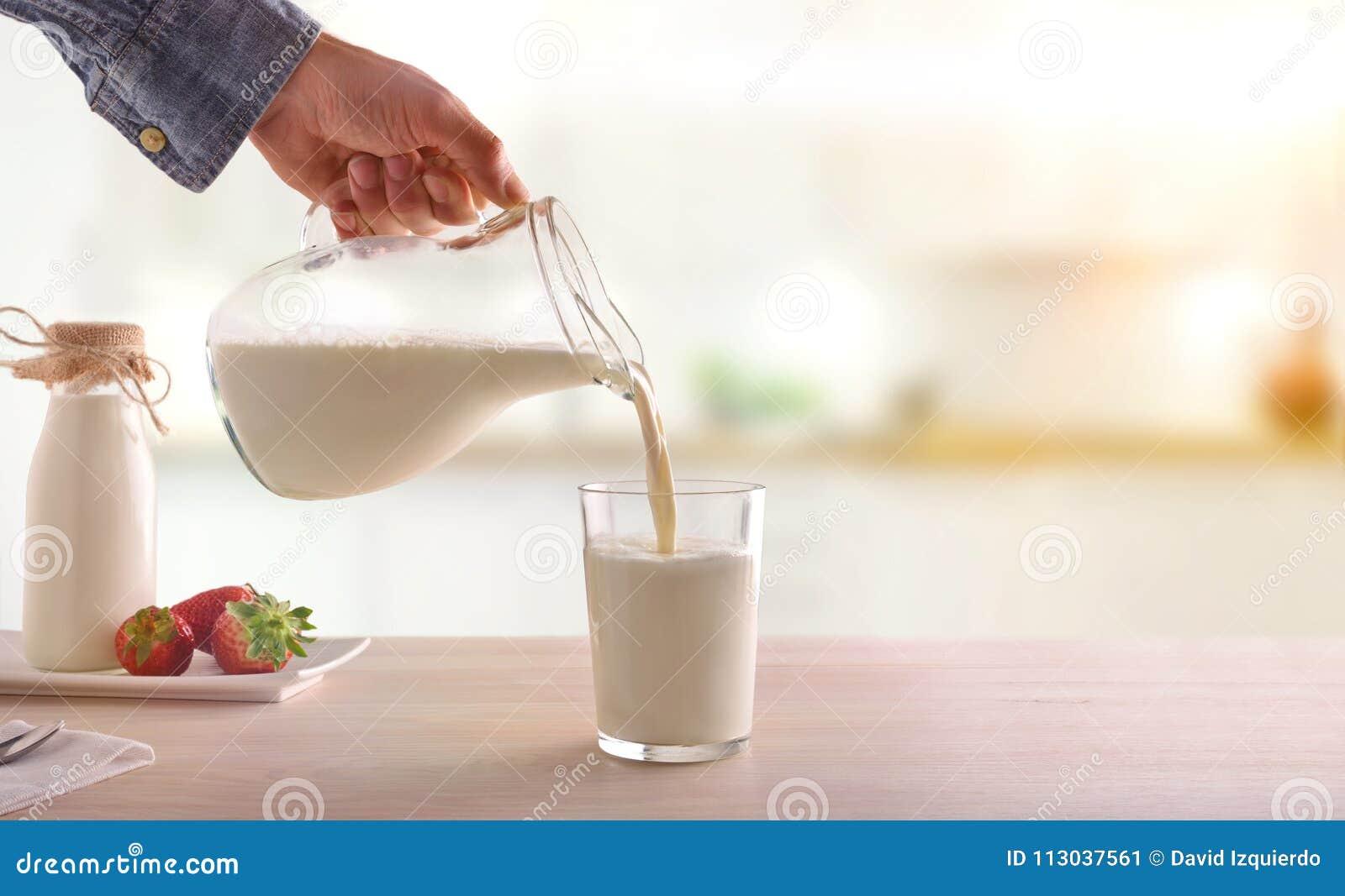 Den tjänande som frukosten mjölkar med en tillbringare i ett exponeringsglas på ett vitt träK