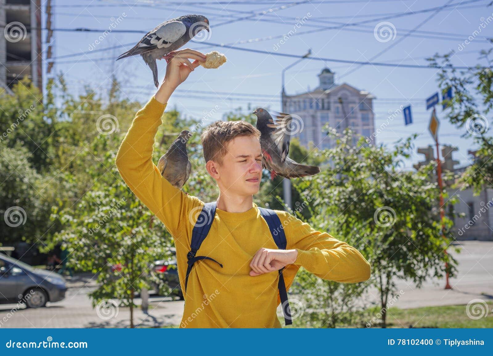 Den tonåriga pojken matar duvor på stadsgatan