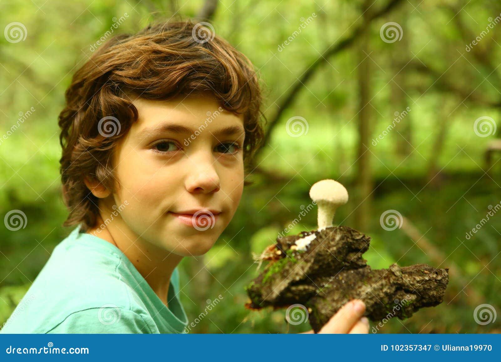 Den tonåriga pojken med regn plocka svamp i skogen