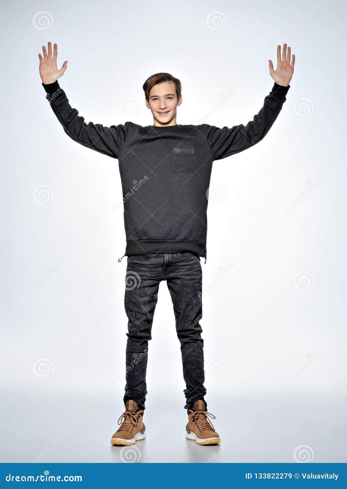 Den tonåriga pojken står på studion med lyftta armar Bekläda beskådar