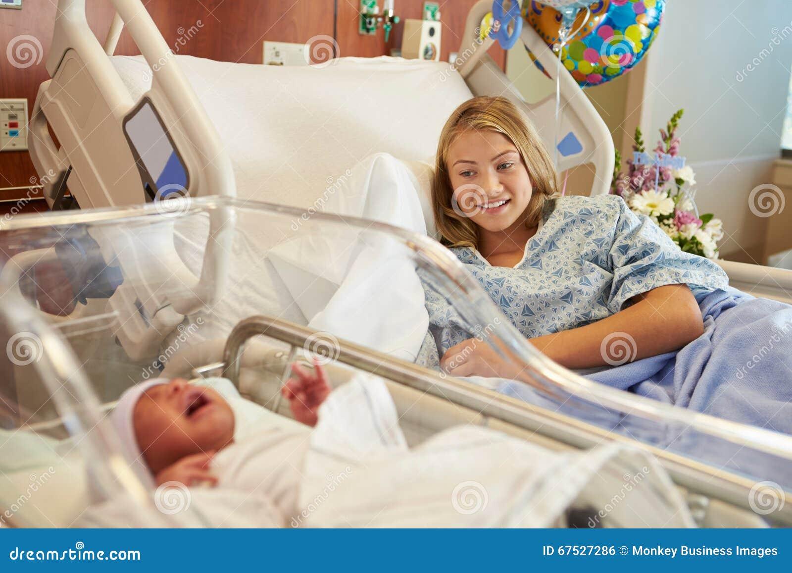 Den tonårs- flickan med nyfött behandla som ett barn sonen i sjukhus