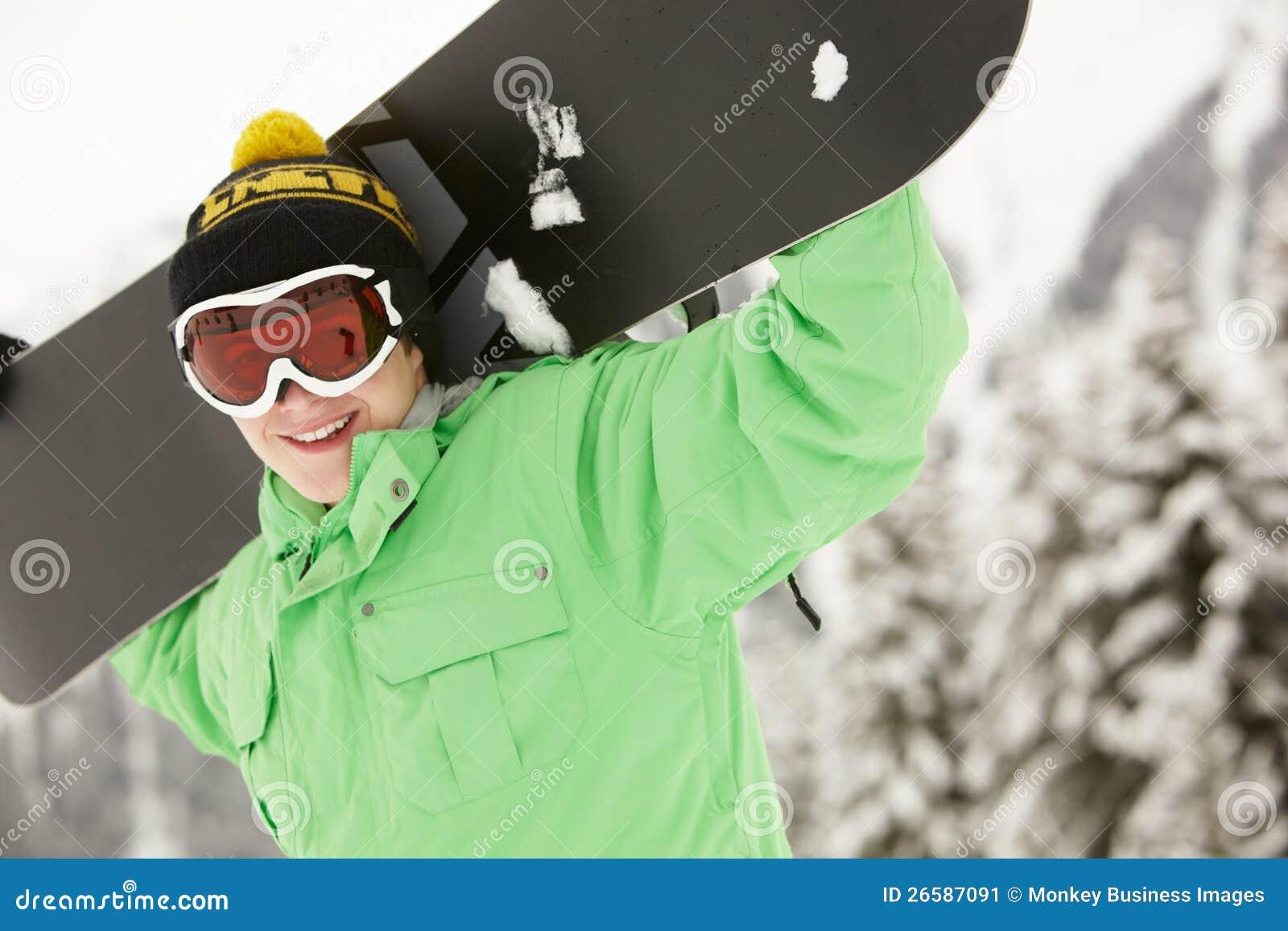 Den tonårs- pojken med snowboarden skidar på ferie