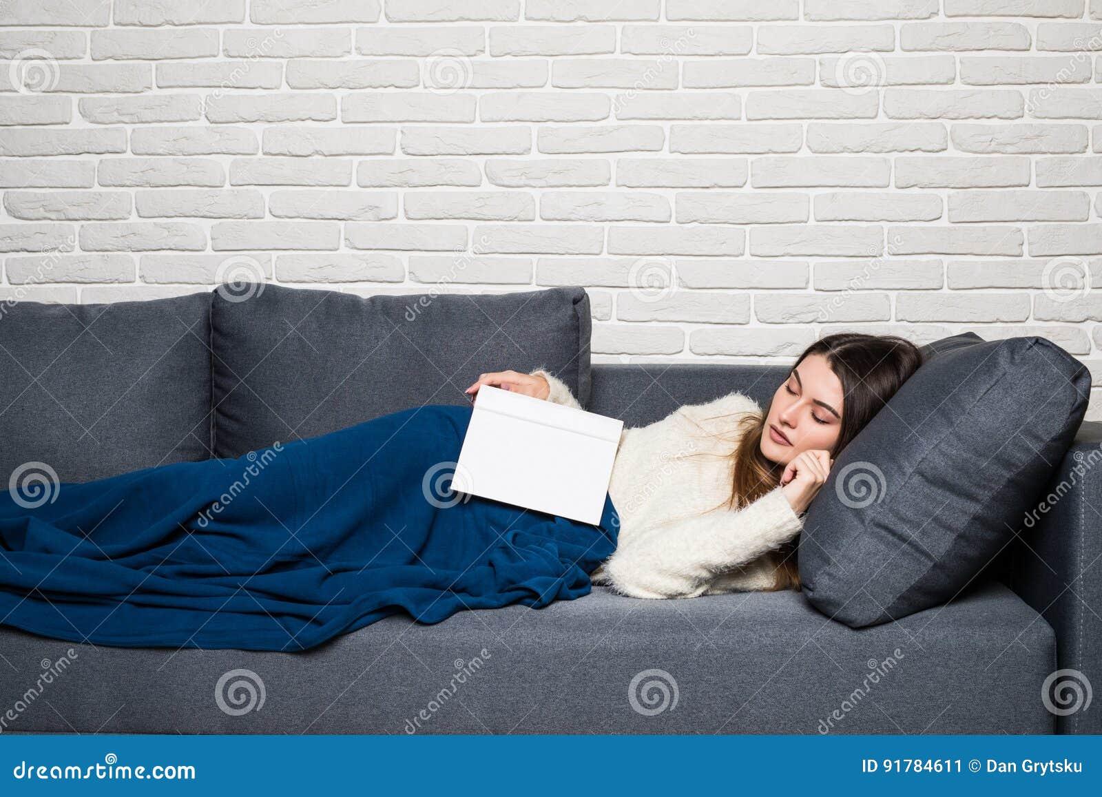Den trötta unga kvinnan som tar en ta sig en tupplur hemmastatt ligga på en soffa med en bok som ligger över hennes bröstkorg och