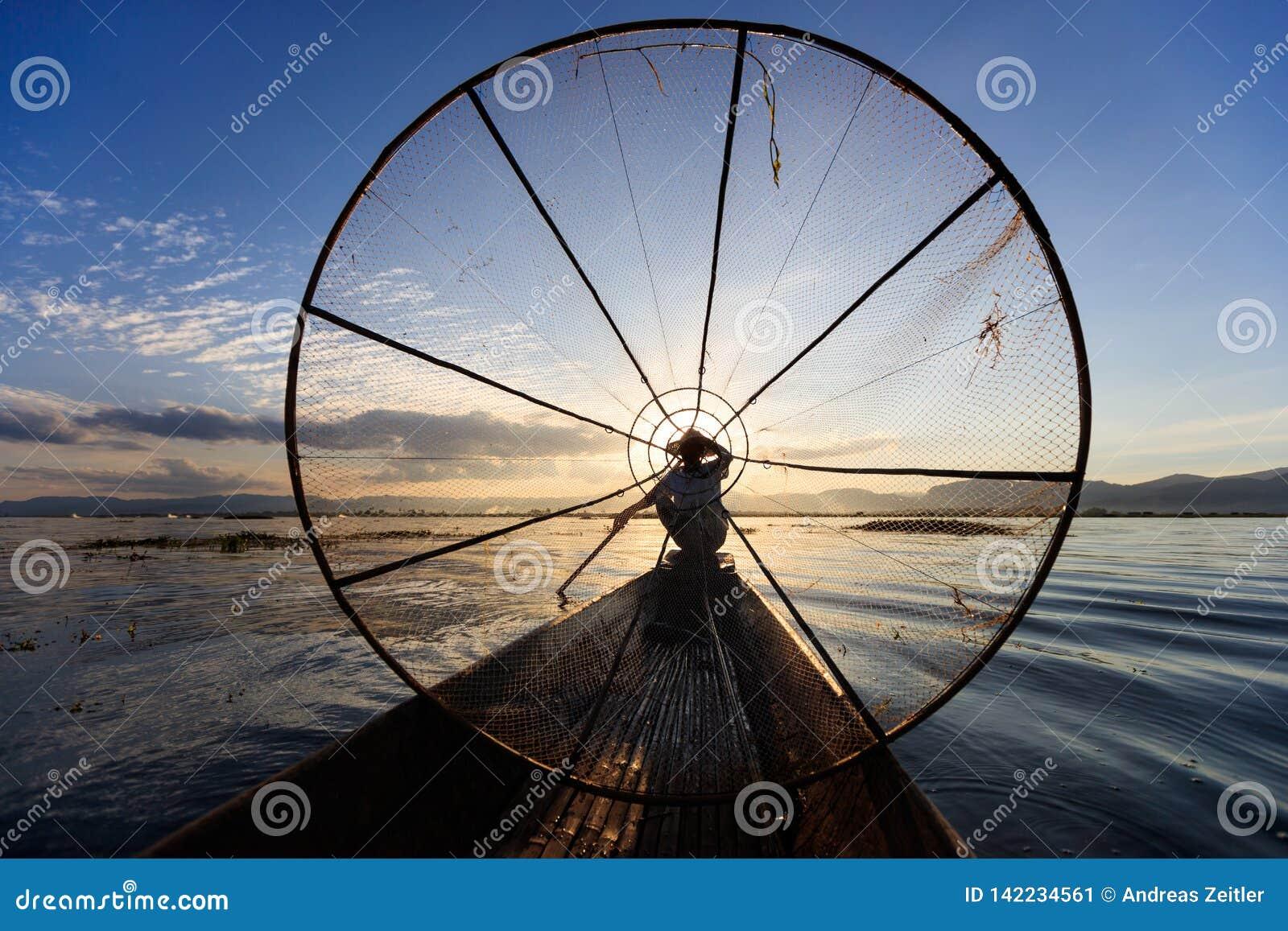 Den traditionella Burmese fiskaren på Inle sjön, Myanmar som var berömd för deras särskiljande, lade benen på ryggen ro stil