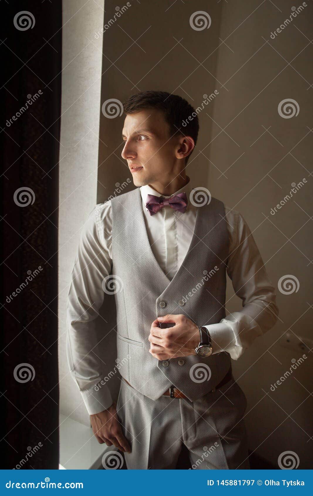 Den trendiga brudgummen förväntar bruden nära fönstret Stående av brudgummen i en grå väst