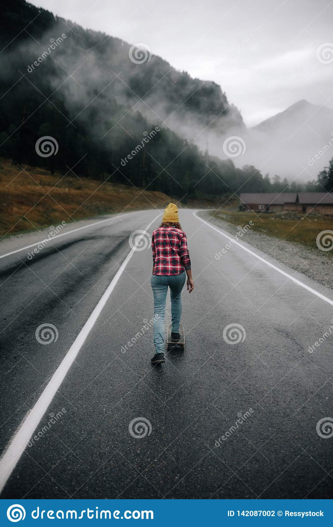 Den trendiga hipsterflickan rider en skateboard på vägen i bergen runt om berget och den härliga sikten